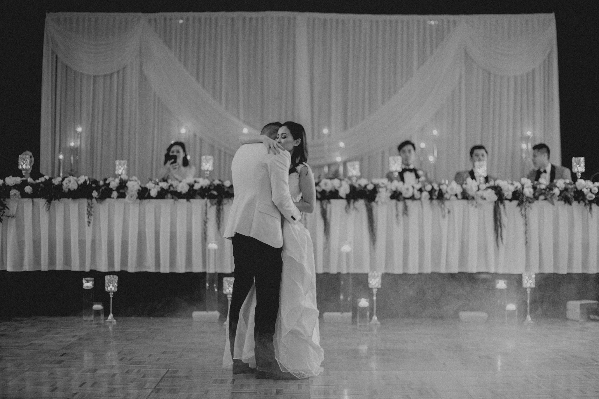 A bride and groom share an intimate hug on the dance floor in front of the bridal table