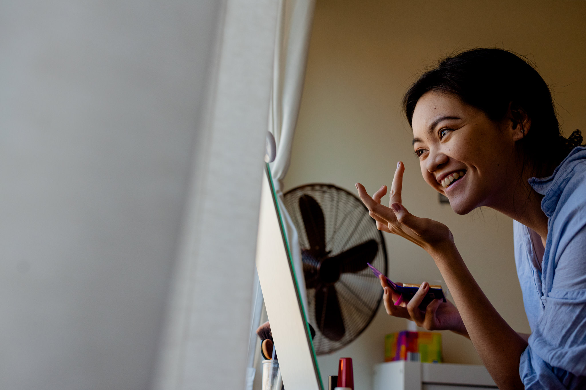Asian girl laughs as she uses her finger to apply makeup next to a window