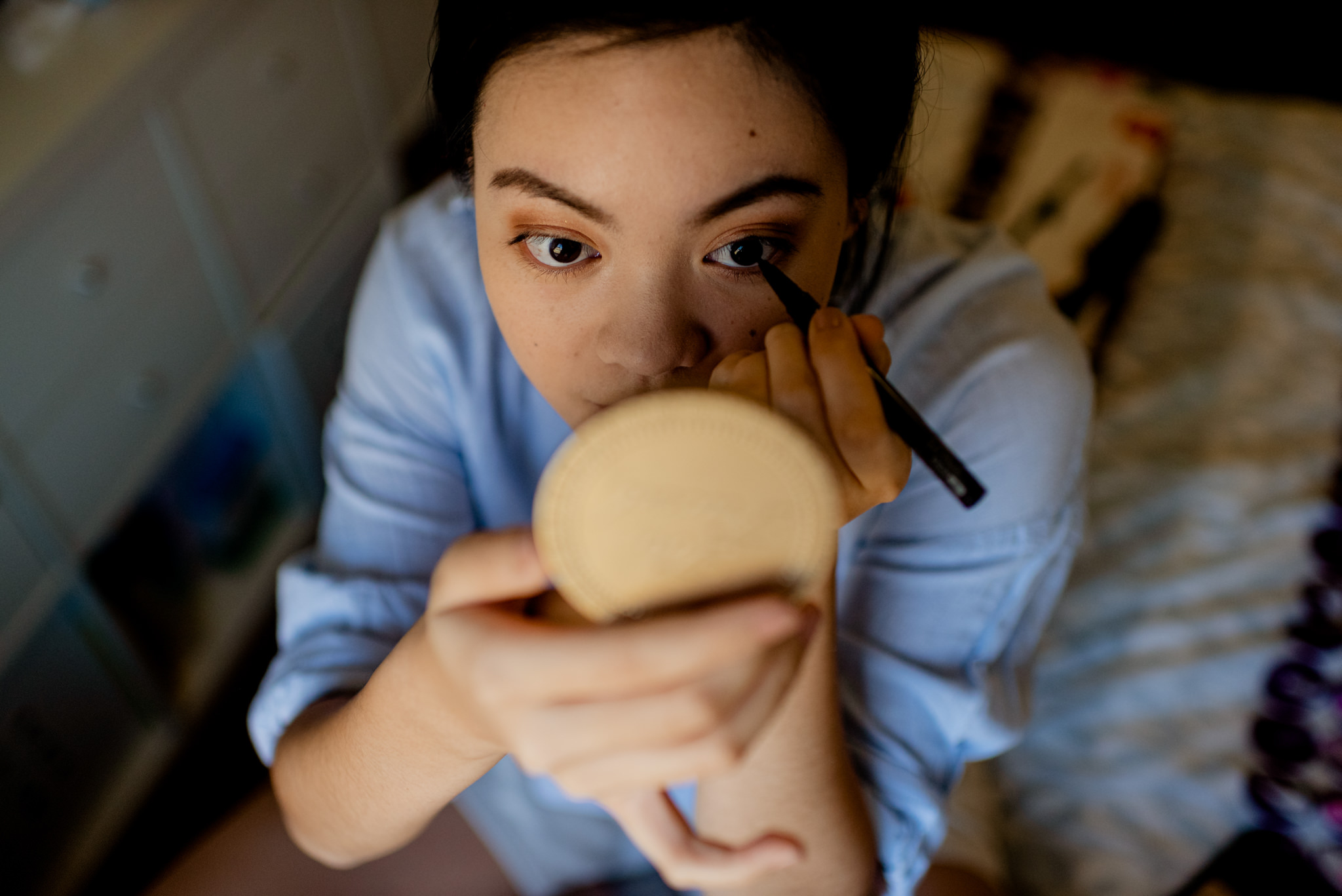 Asian woman draws on eye makeup looking in a handheld mirror
