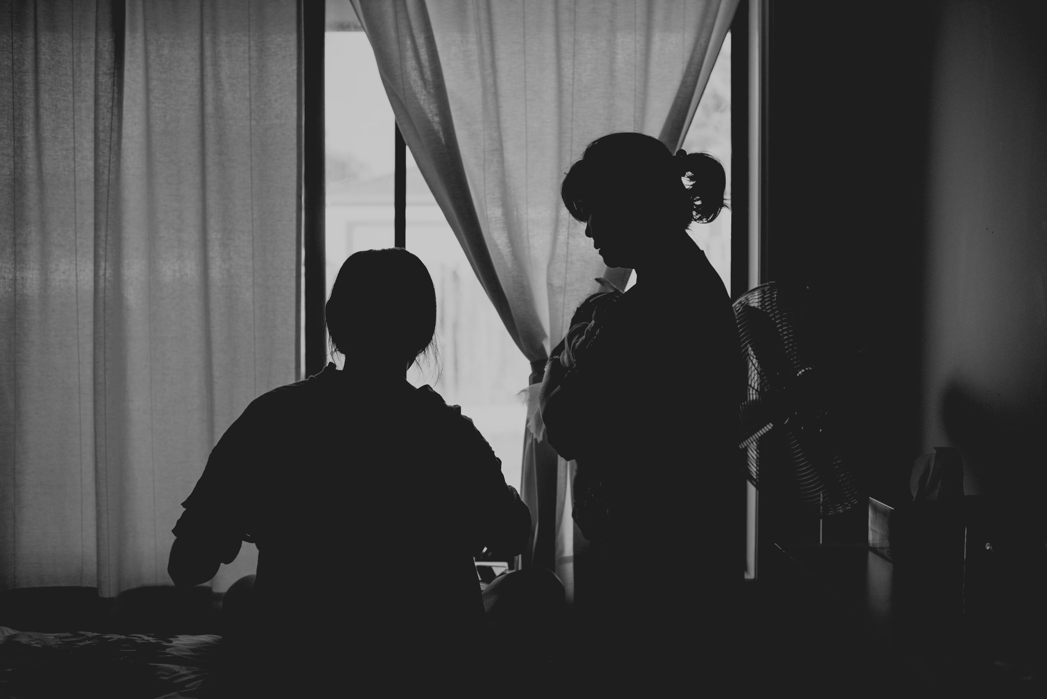 Two silhouettes stand and sit in front of a window