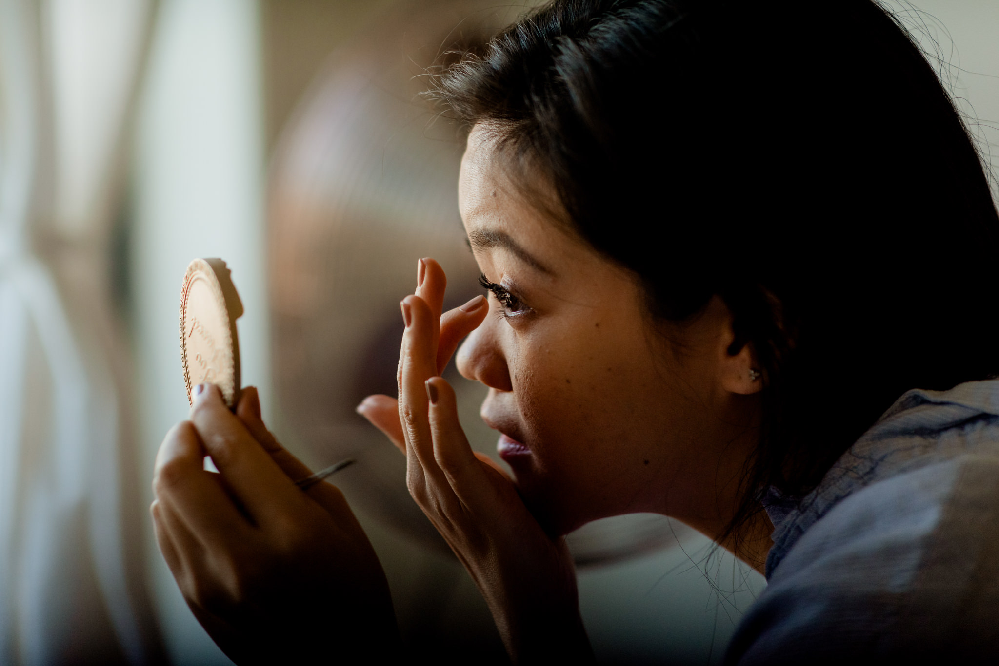 A girl using her fingers to apply eyelashes looking in a handheld pocket mirror