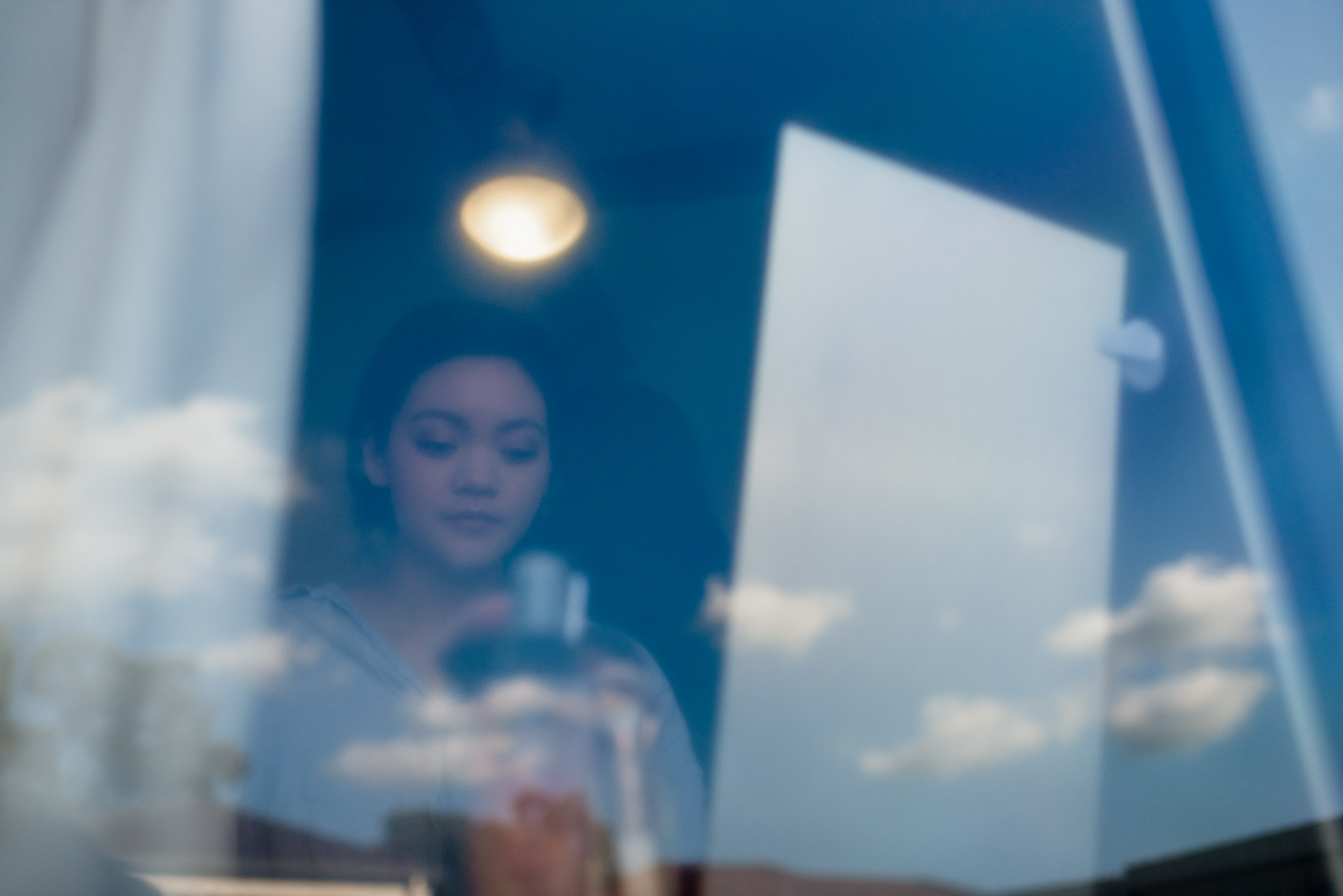 A photo through a window of an asian girl sitting in front of a mirror with a cloudy blue sky reflecting on the window