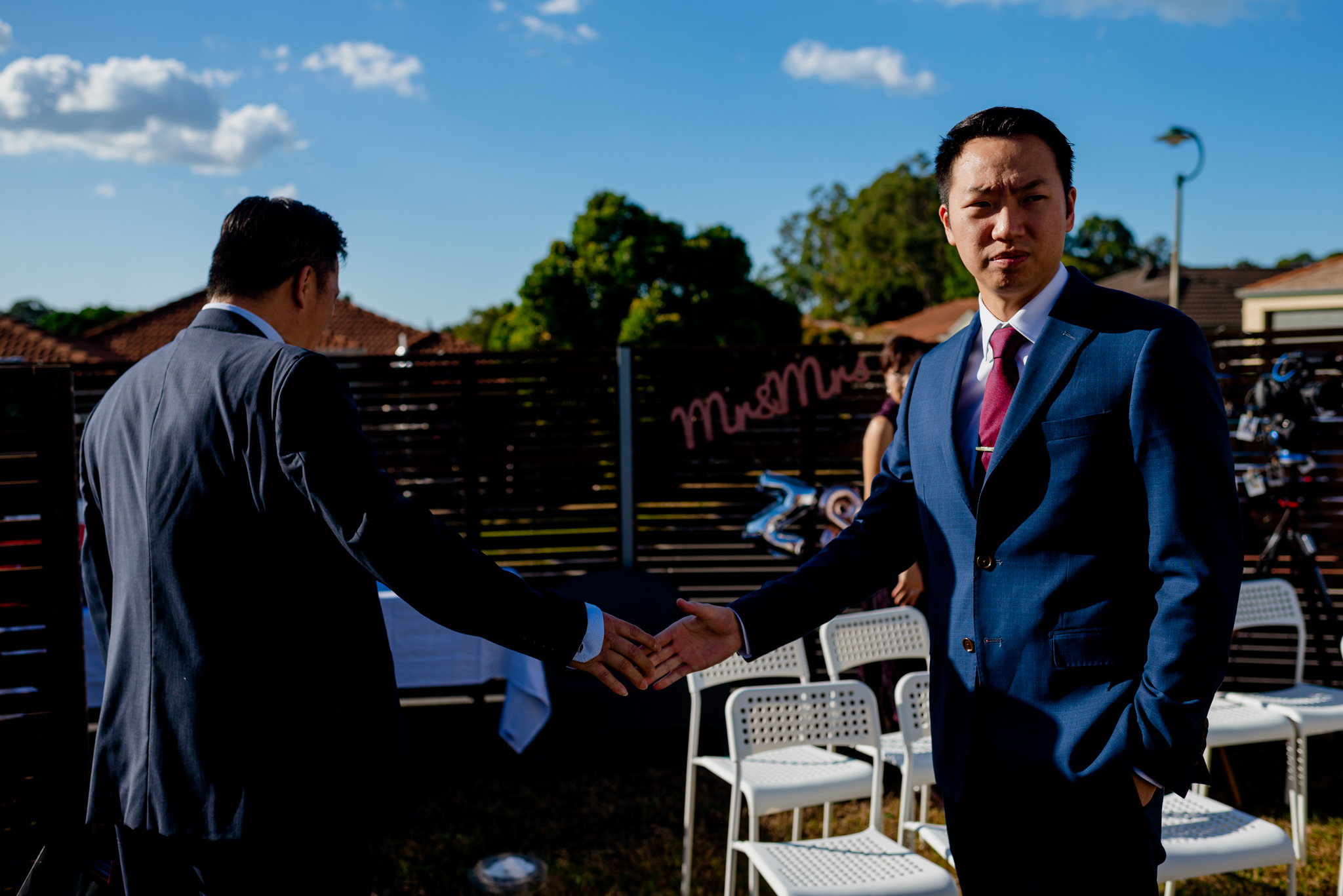 Two asian men in suits look serious and pass by each other and shake hands