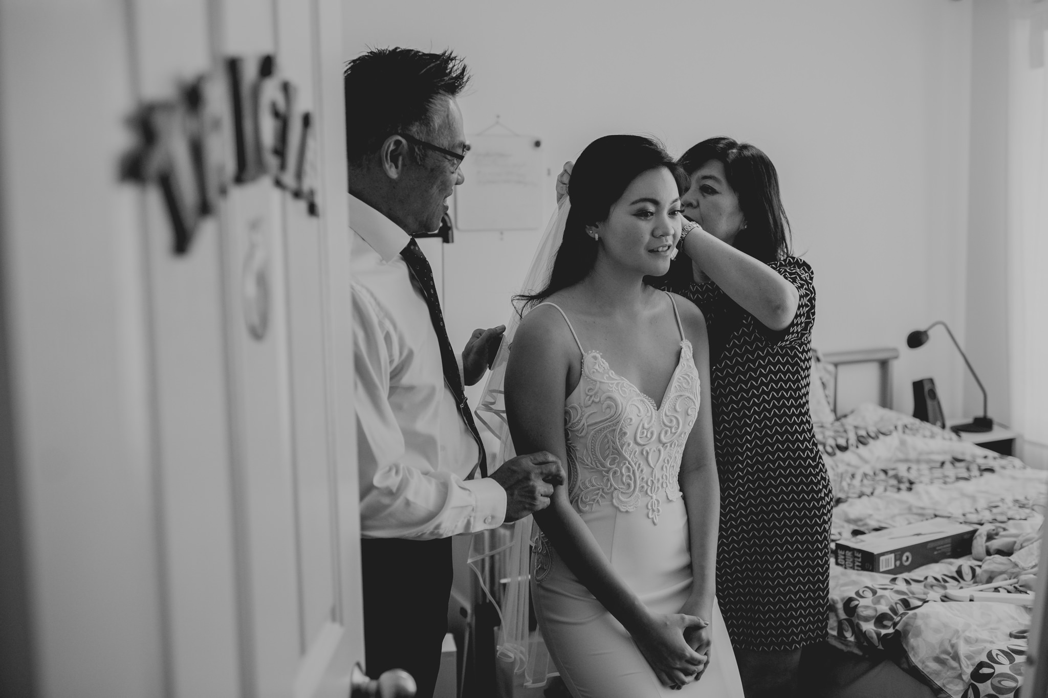 A mother and father help a bride put a wedding veil in her hair