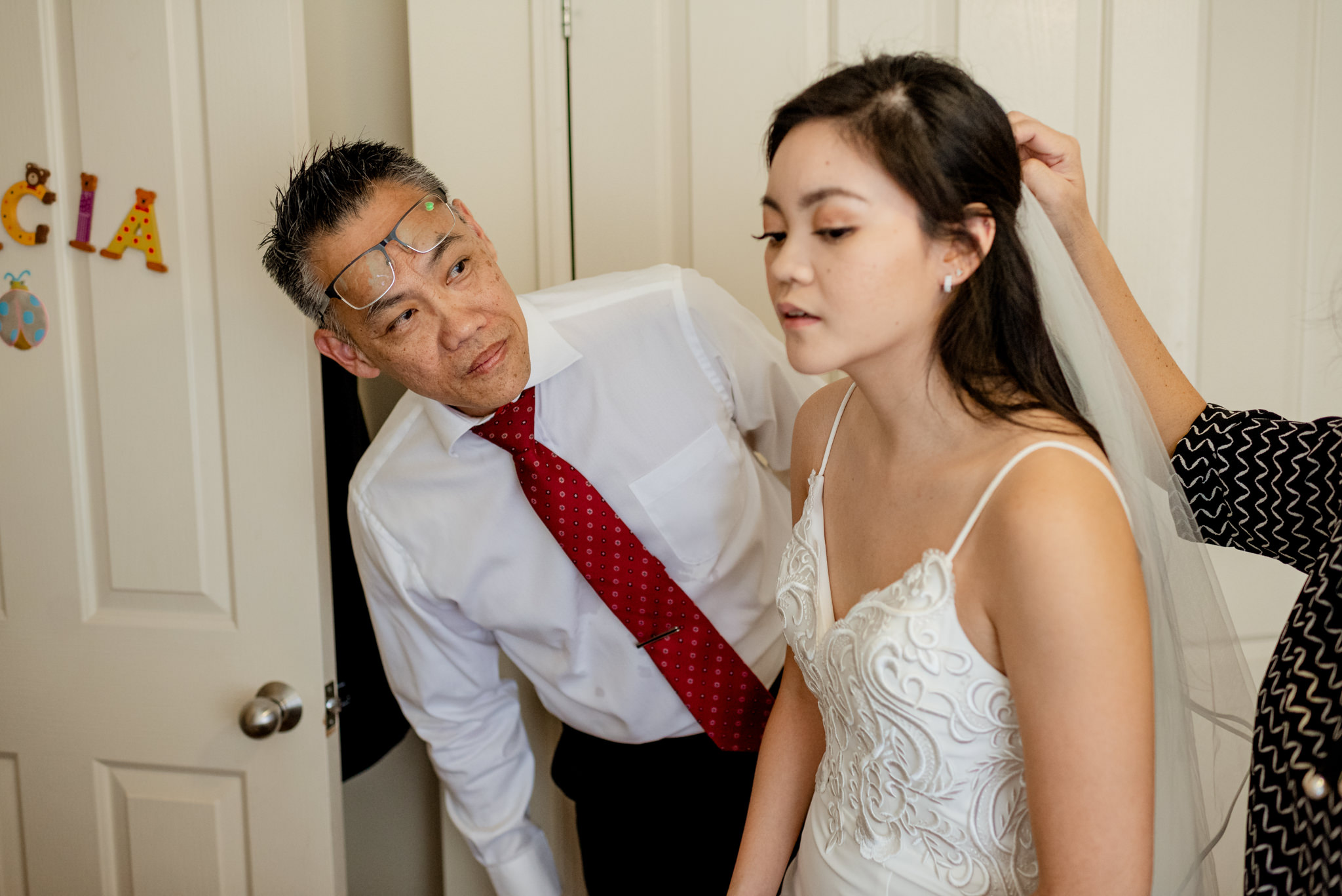 The father-of-the-bride tilts and looks at his daughter as she has her wedding veil put in her hair