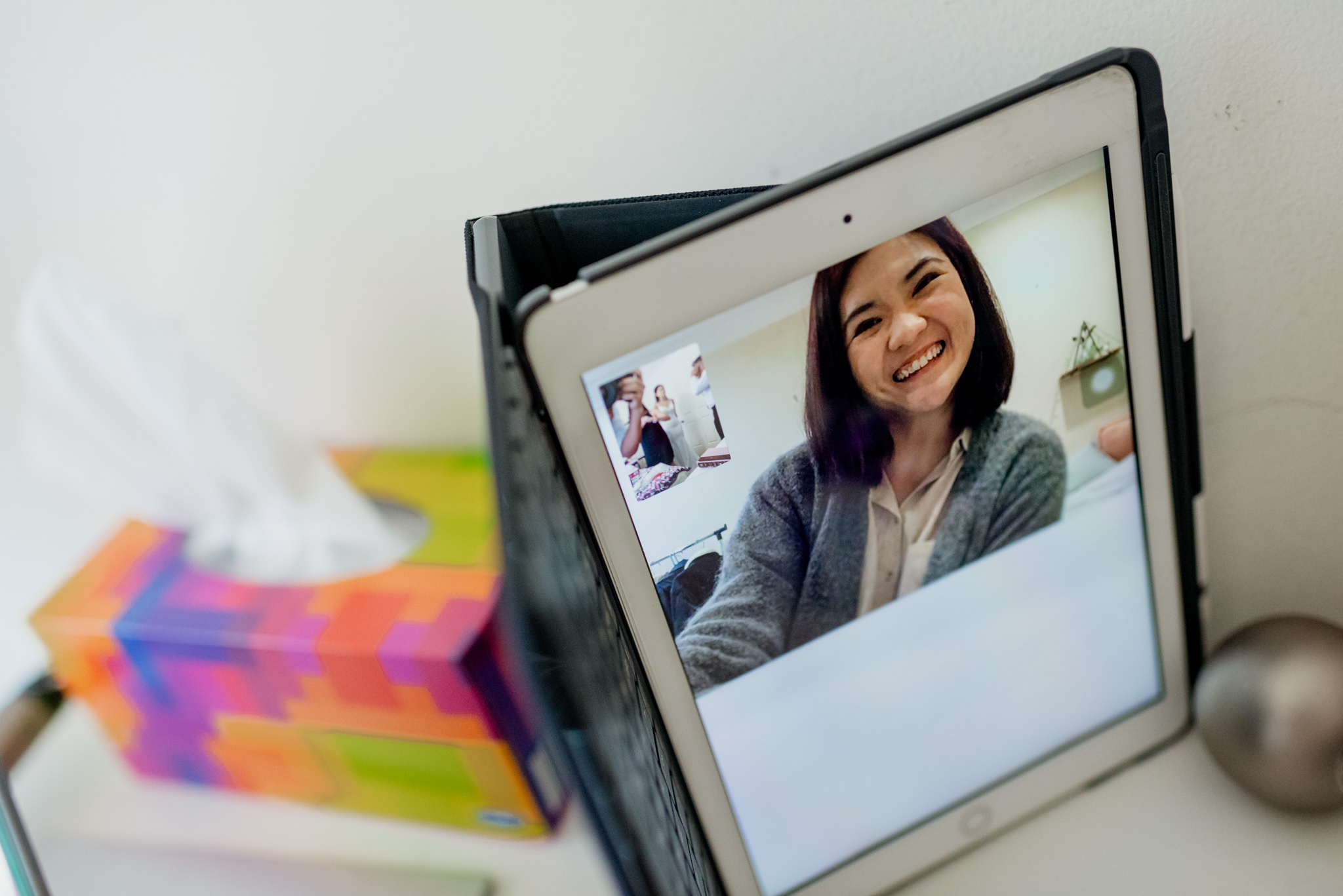 A smiling woman video calling on an Ipad placed next to a tissue box