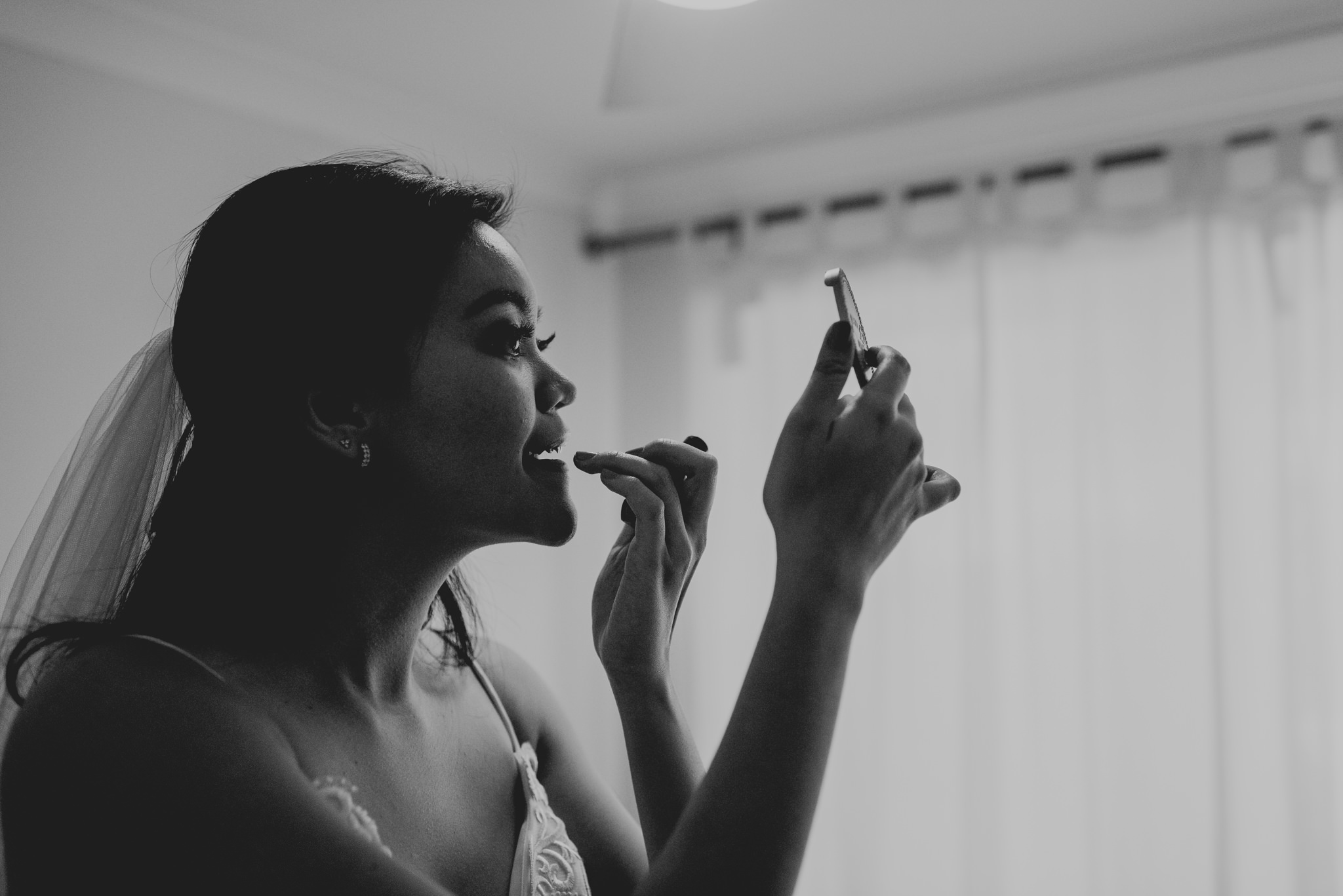 An asian woman applies lipstick with her fingers as she looks at a small mirror