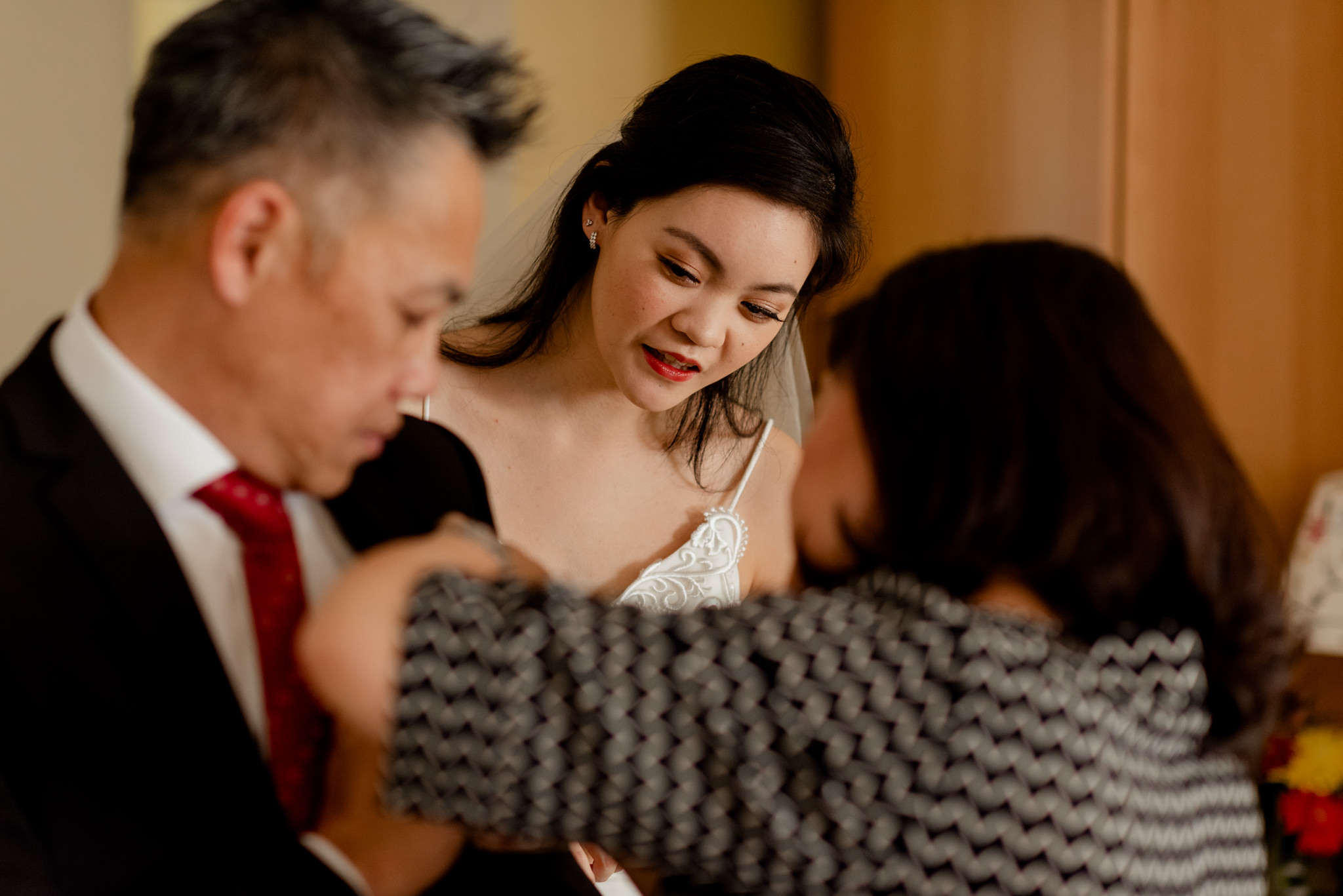 An Asian bride looks at her parents attempting to put a boutineer on a suit