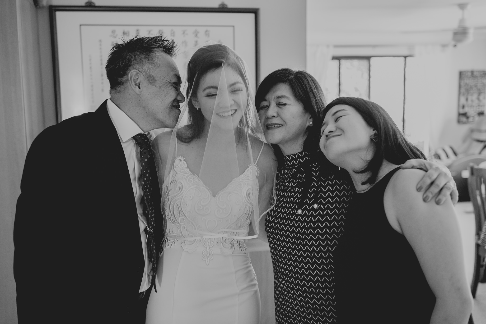 An asian family hugs each other, one of the daughters is in a wedding dress and veil