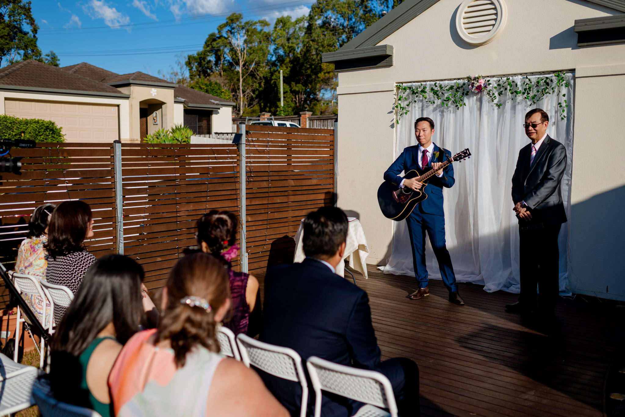 A groom holding a guitar and a celebrant stand in front of a small gathering of people sitting on a wooden deck