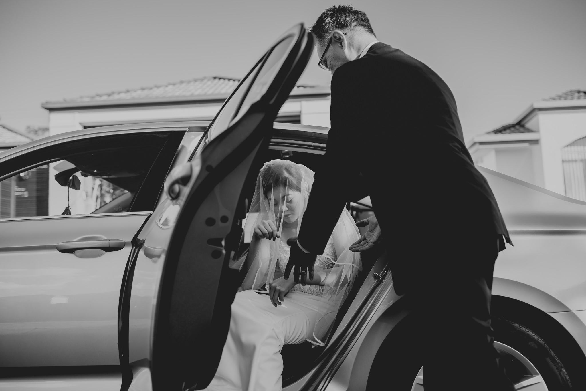 A man reaches his hands out to assist a bride out of a white car
