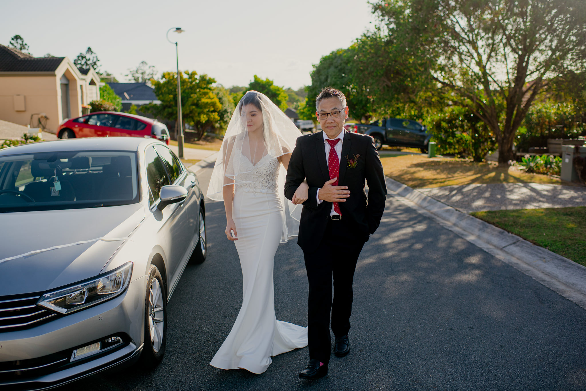 An Asian bride and her father link arms and walk down a road