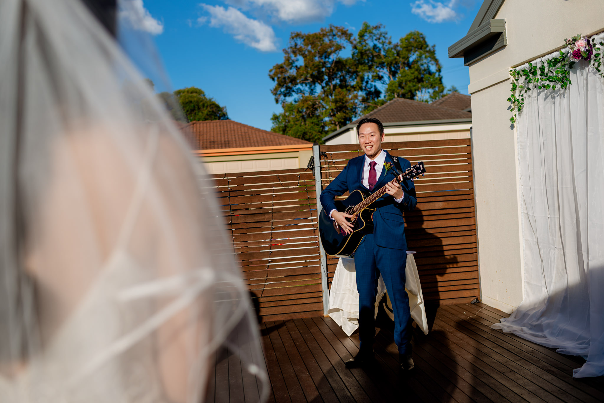 A groom plays guitar and sings on a wooden deck in front of a house