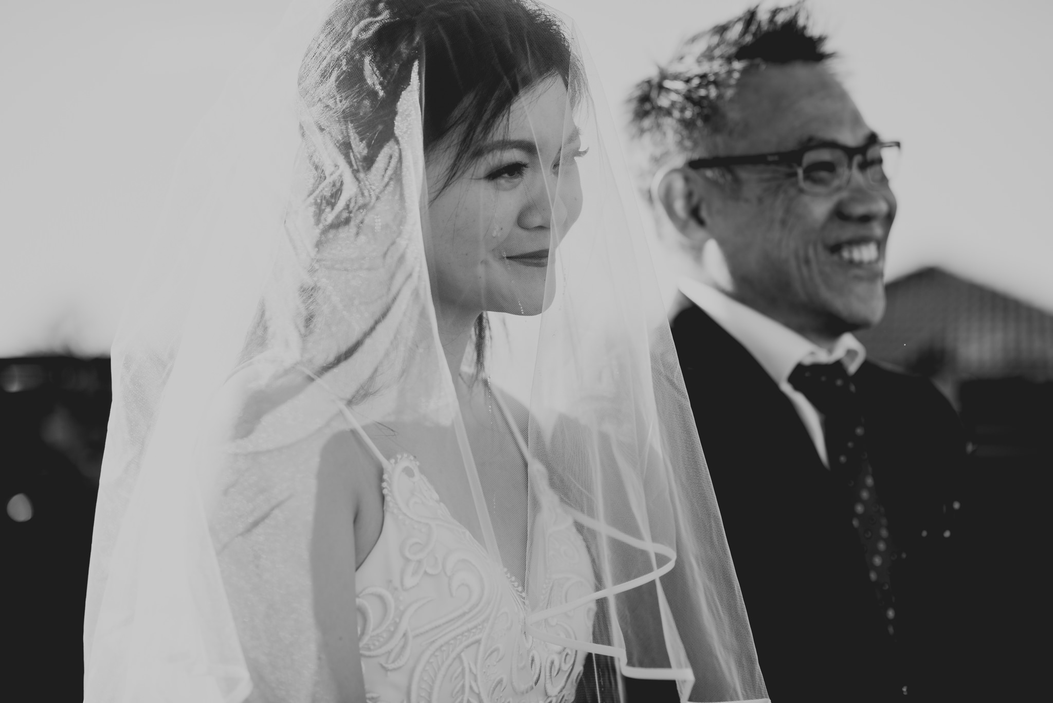 A bride cries and smiles next to her laughing father