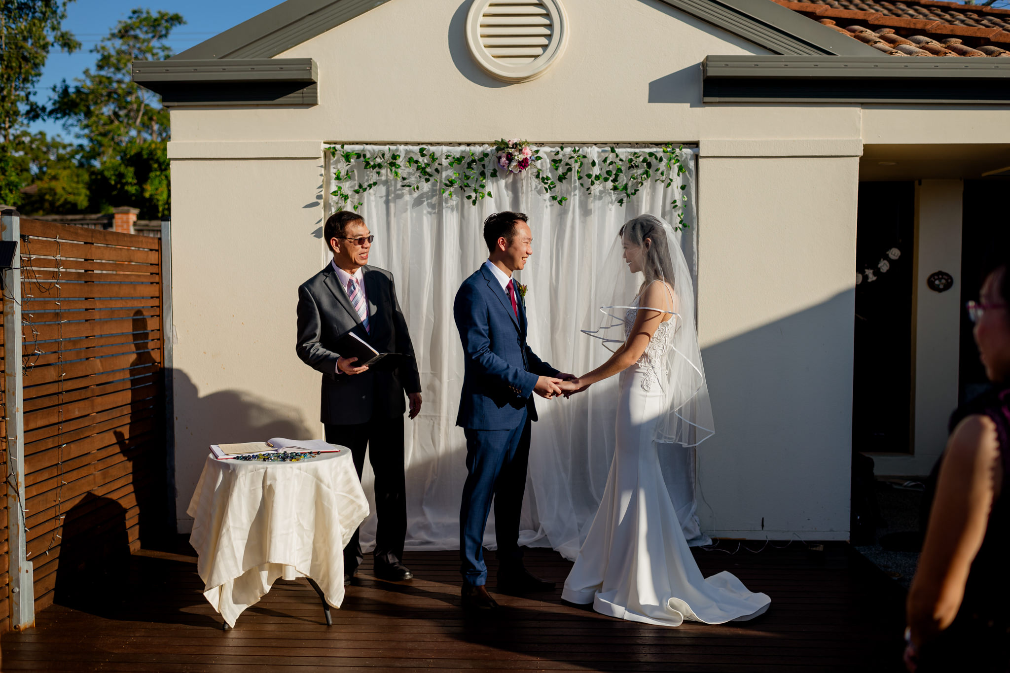 A bride and groom hold hands next to a pastor in front of a home