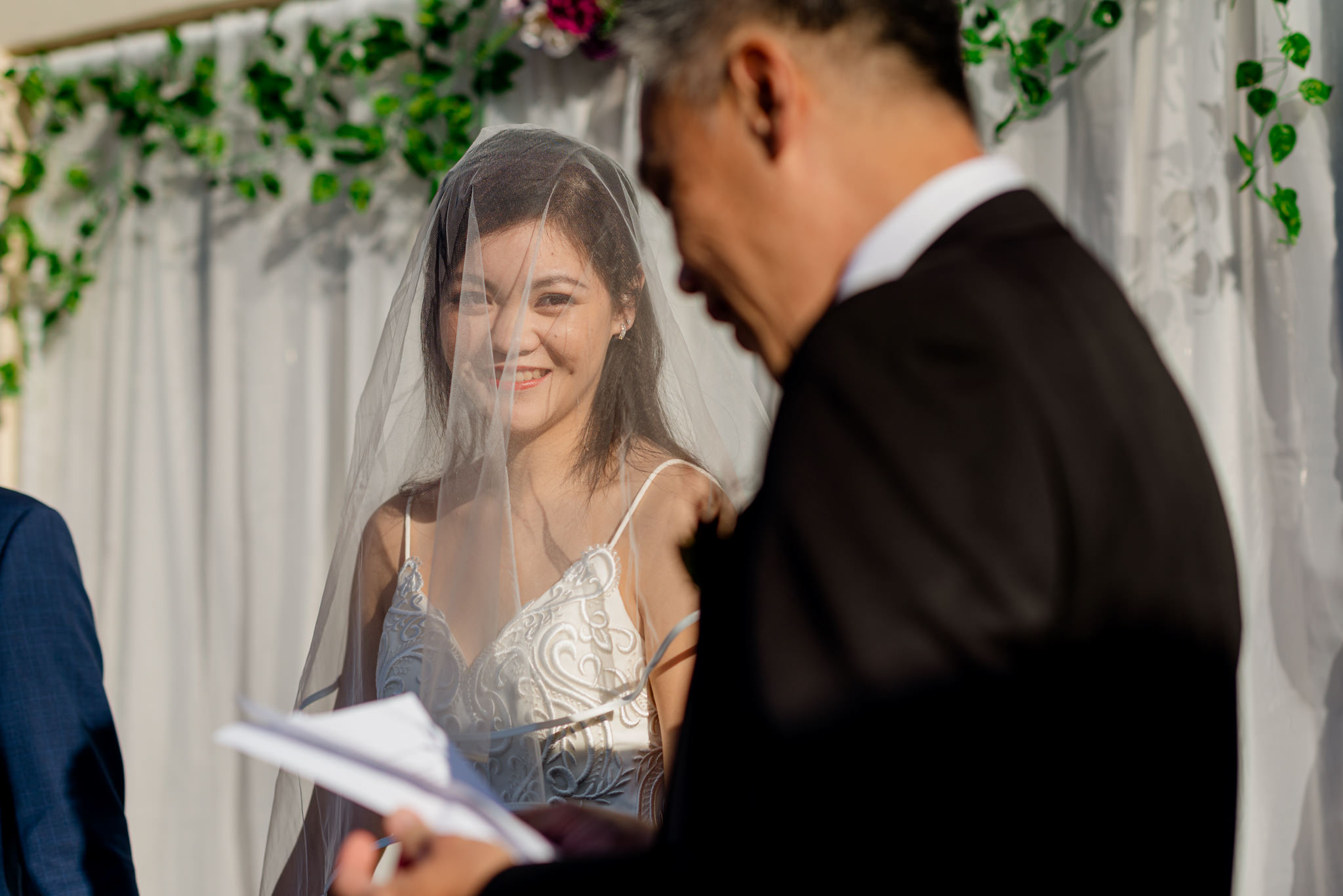 A bride smiles at a man delivering a speech at a wedding