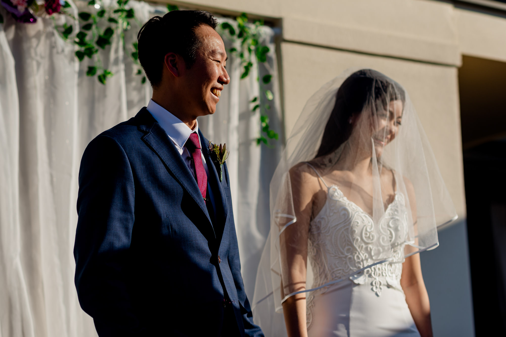 A laughing bride and groom during their outdoor wedding ceremony