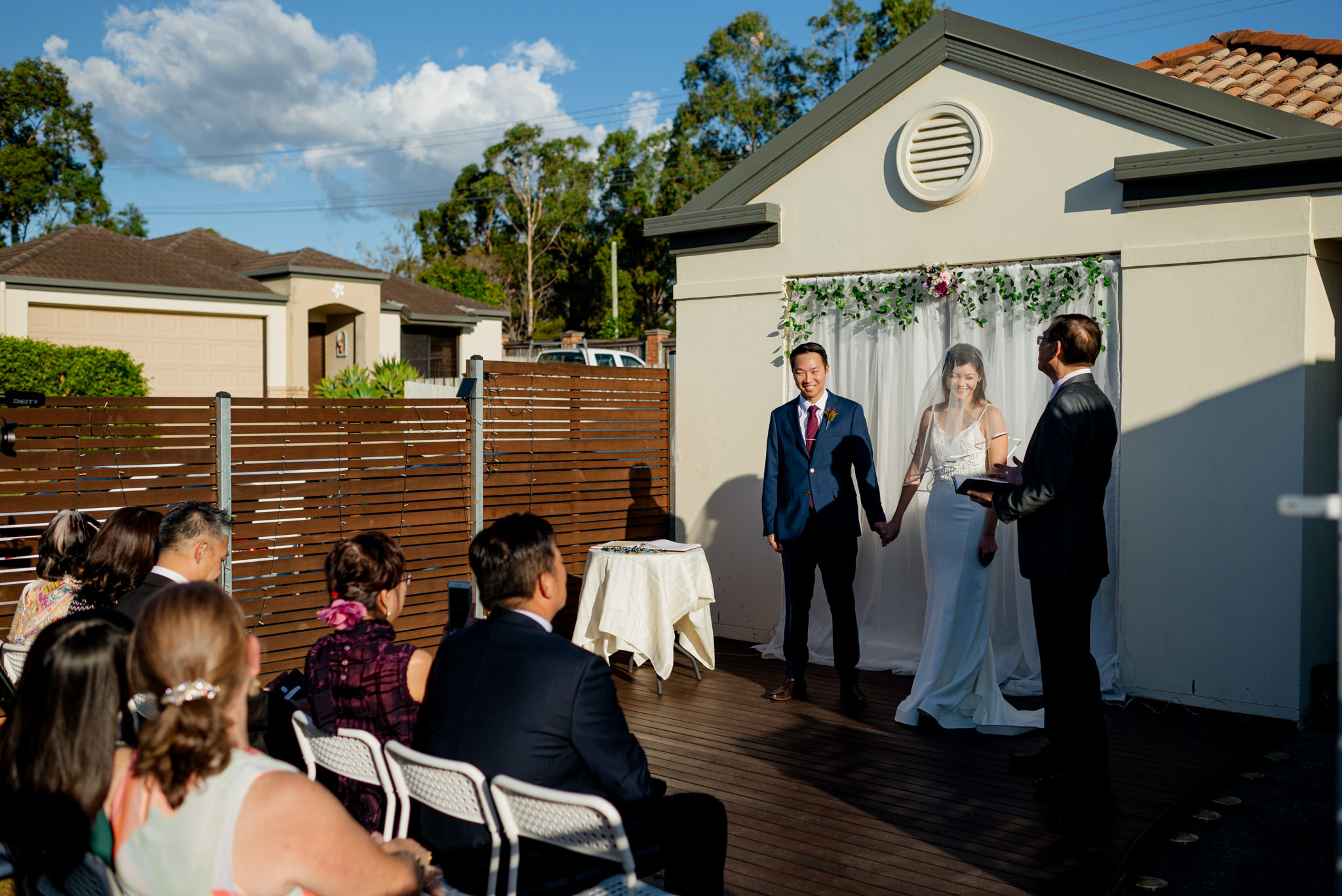A small wedding ceremony held in a suburban home's front porch
