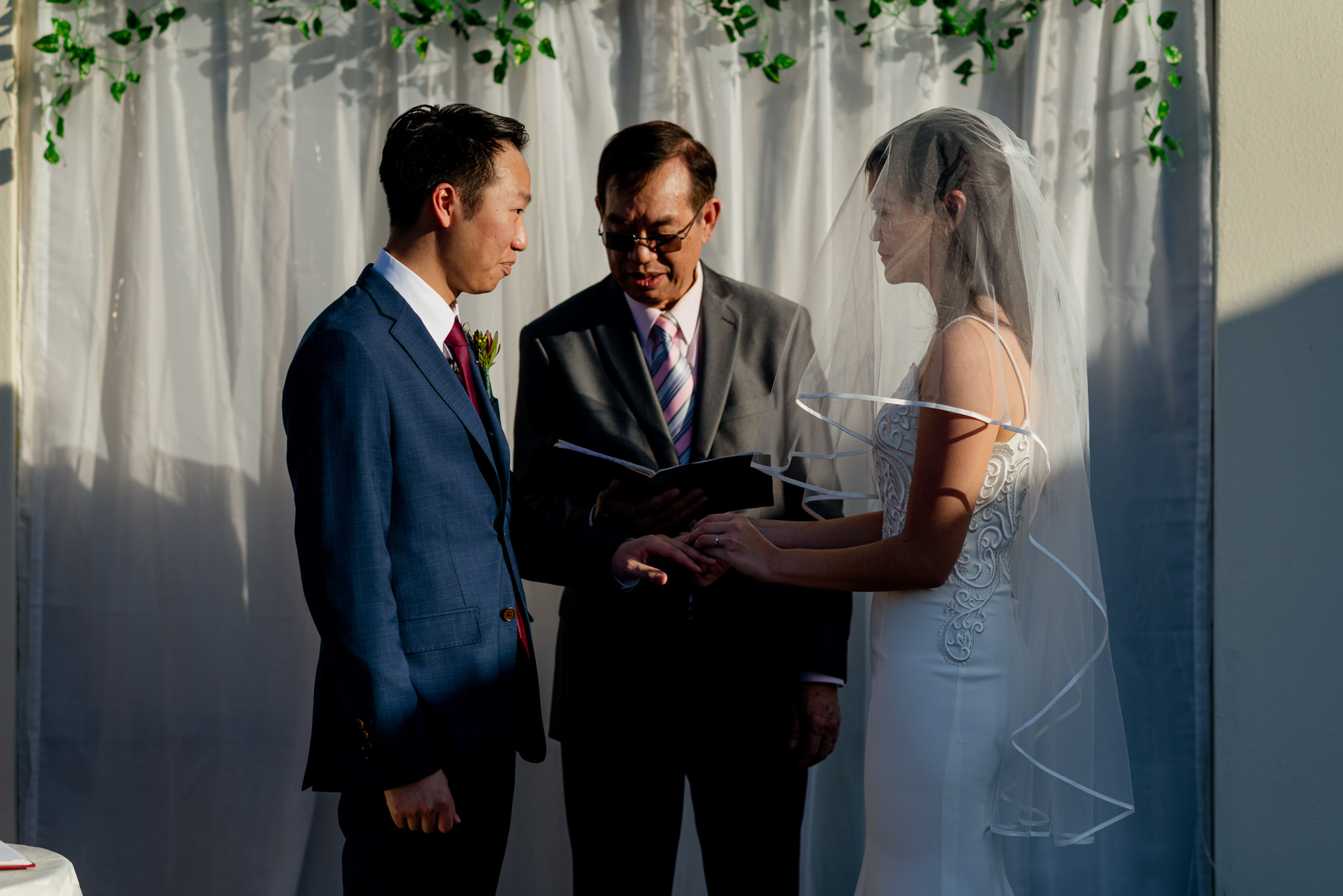 An Asian bride places a wedding ring on her groom's finger during their wedding ceremony