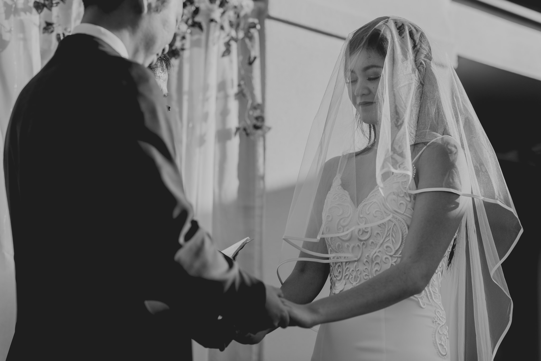 A bride closes her eyes as she holds hands with her groom during a wedding ceremony