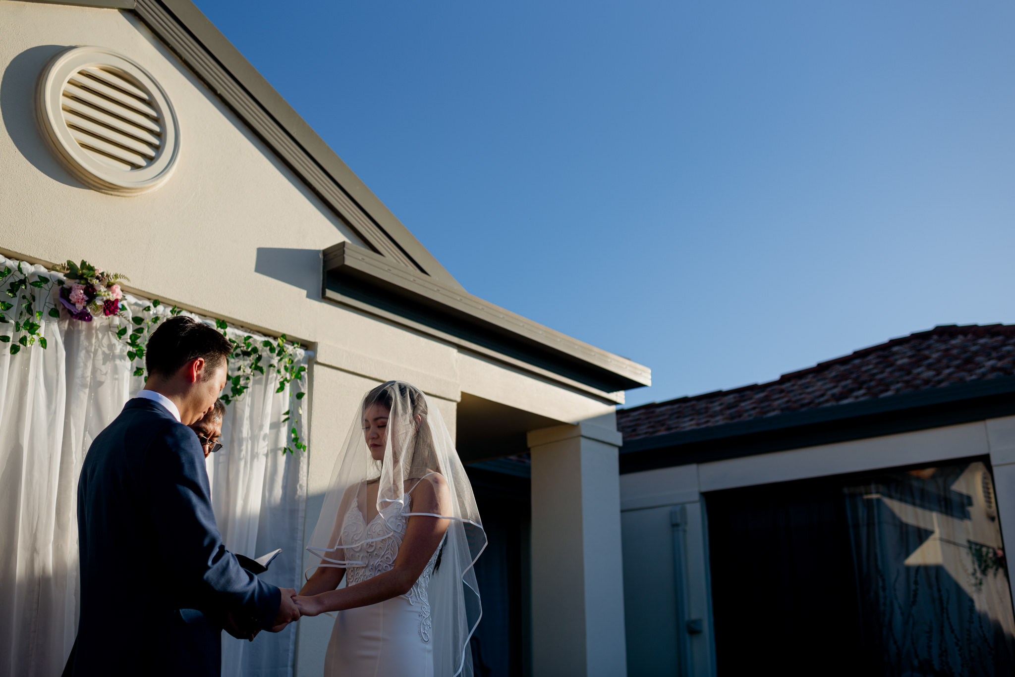 A bride closes her eyes as she holds hands with her groom in front of a small home