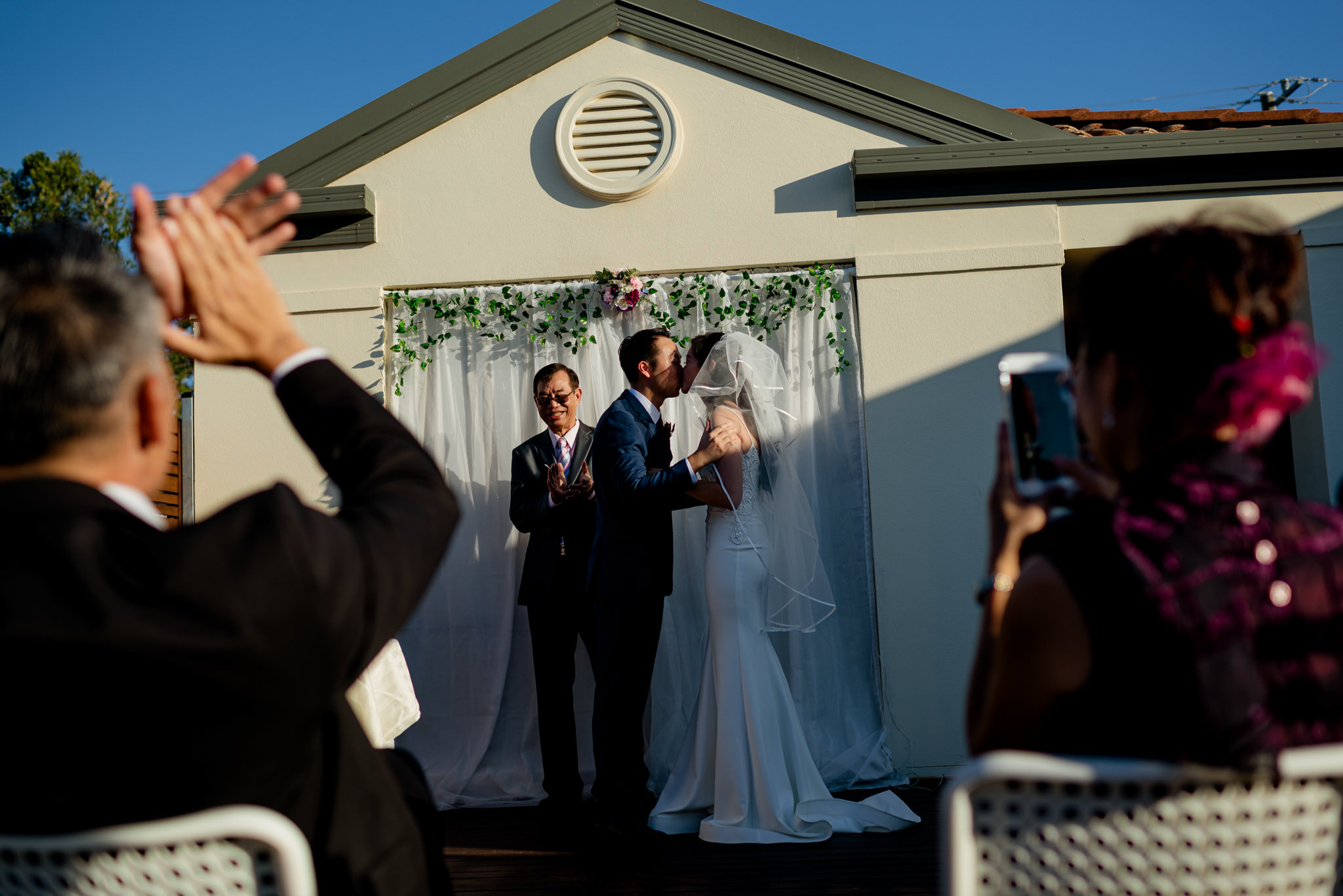 Onlookers clap as a bride and groom share a first kiss