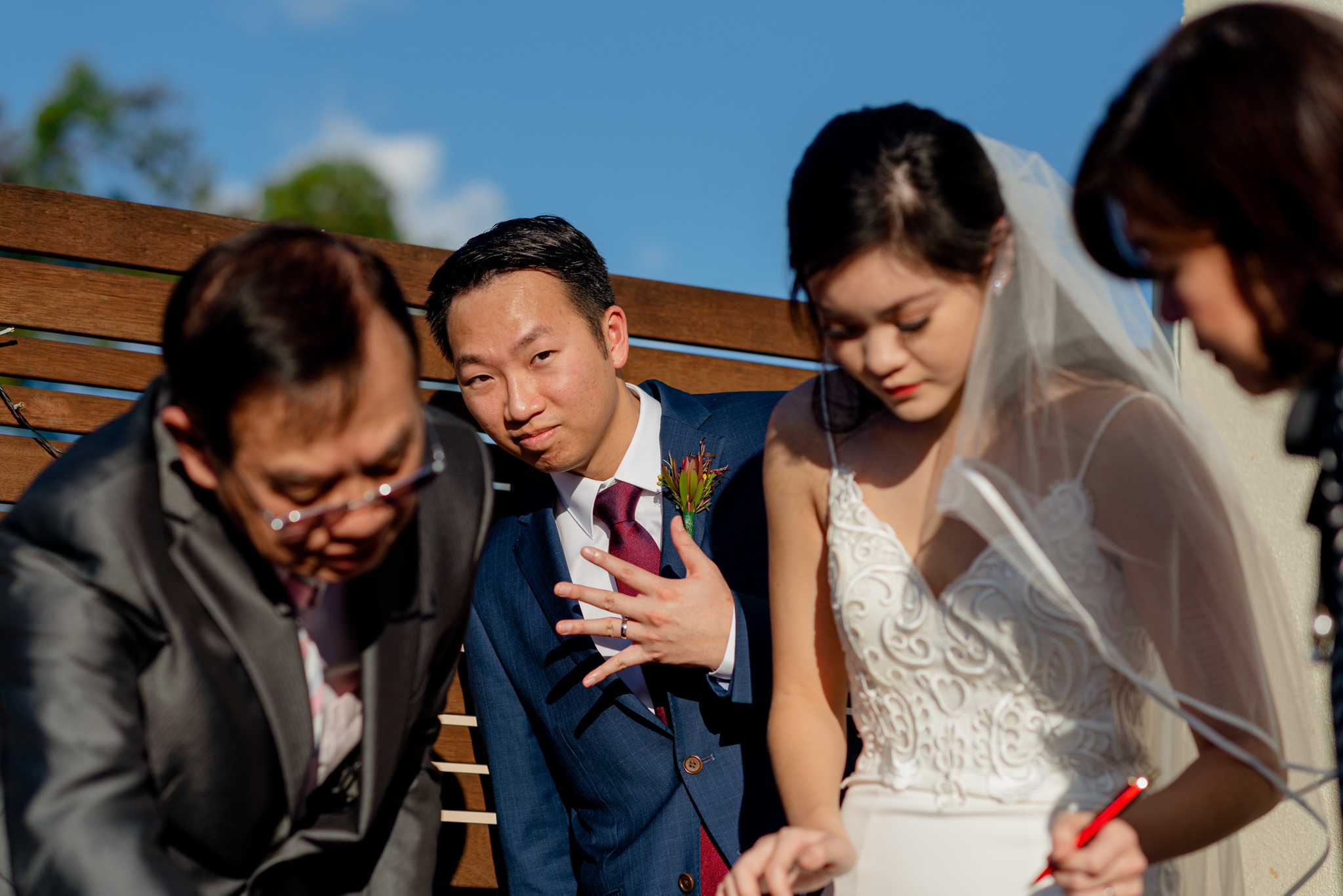 An Asian groom shows the camera his outstretched hand as his bride signs wedding papers