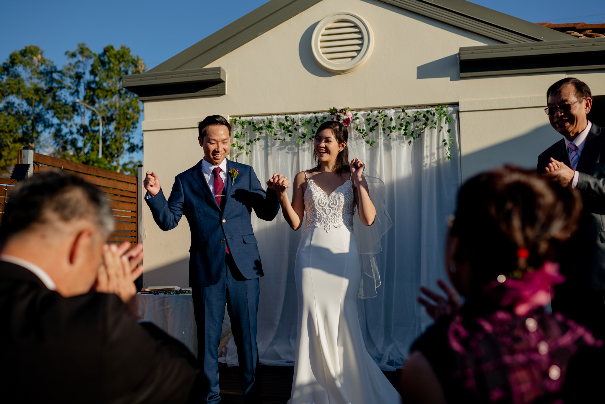 Two newlyweds laugh and cheer with their fists in the air as wedding guests applaud