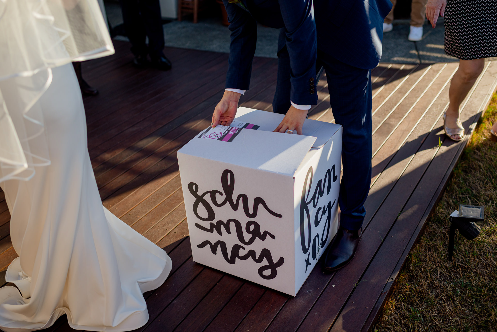 A man opening a large white cardboard box with cursive black text