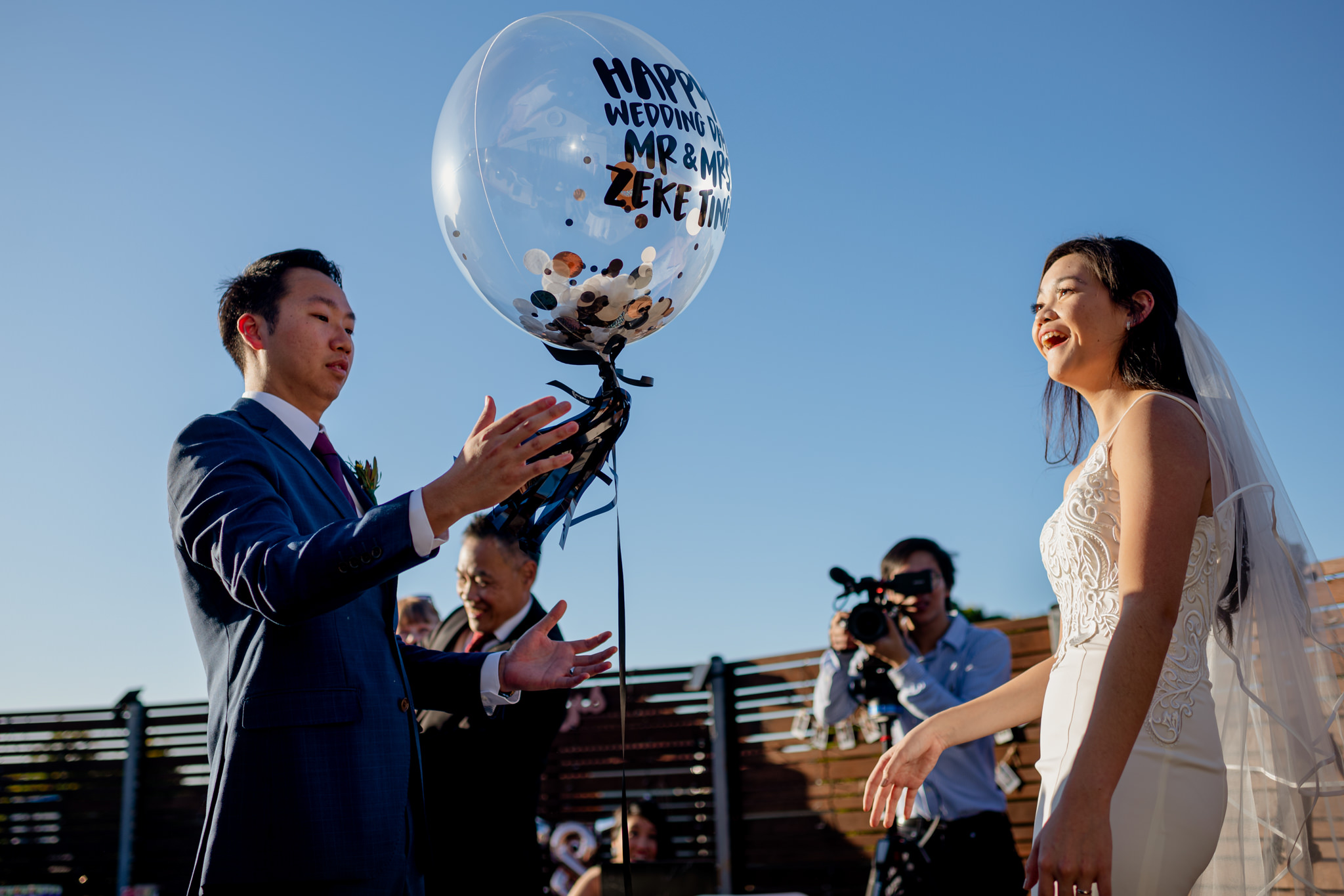 A bride smiles in surprise as a large balloon with text floats in the air
