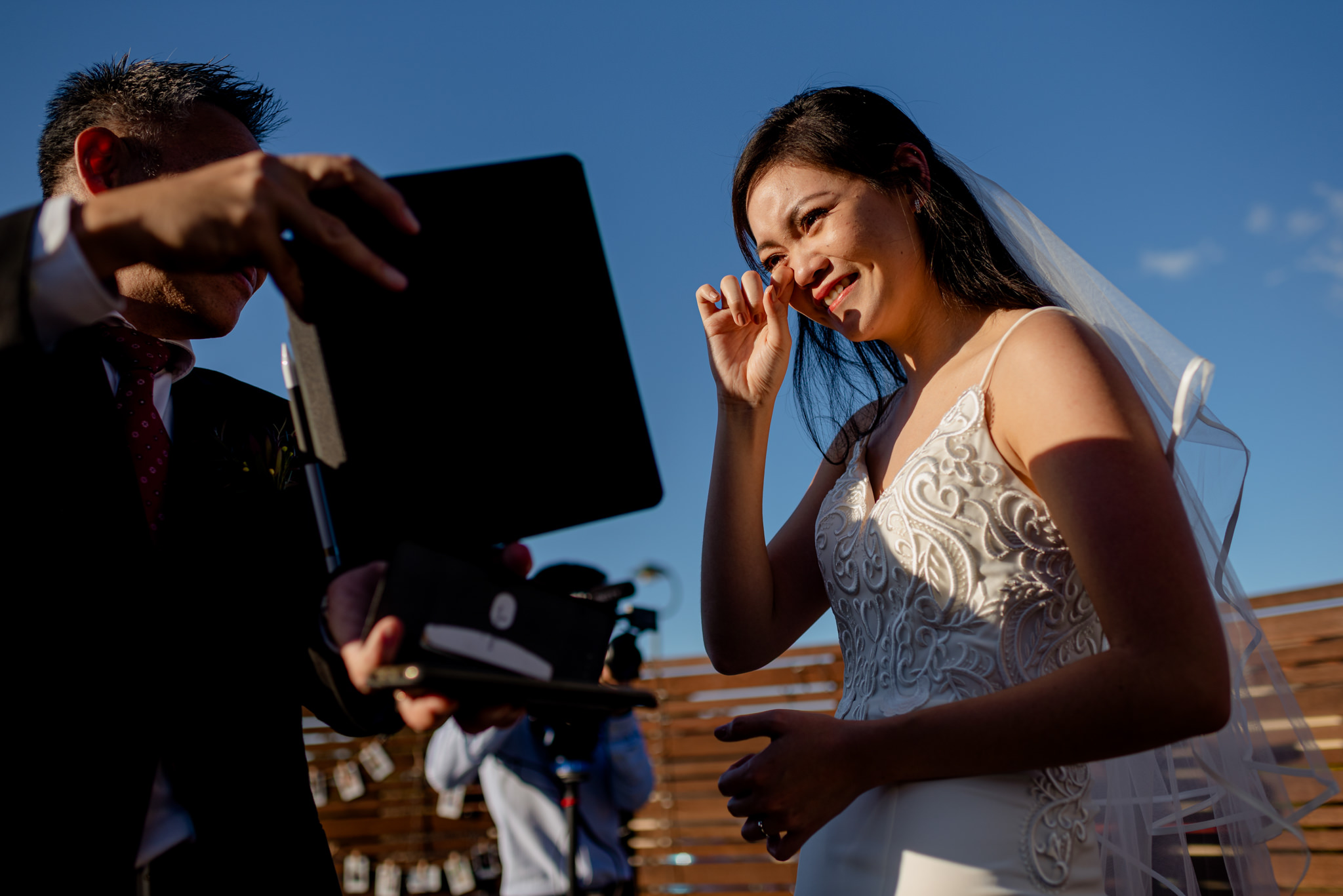 A crying bride wipes away tears as someone shows her a tablet