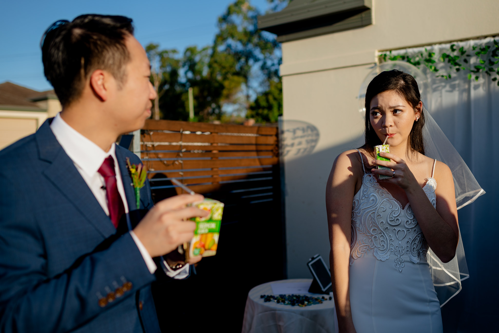 A bride looks at her new husband suggestively as they sip from juice boxes