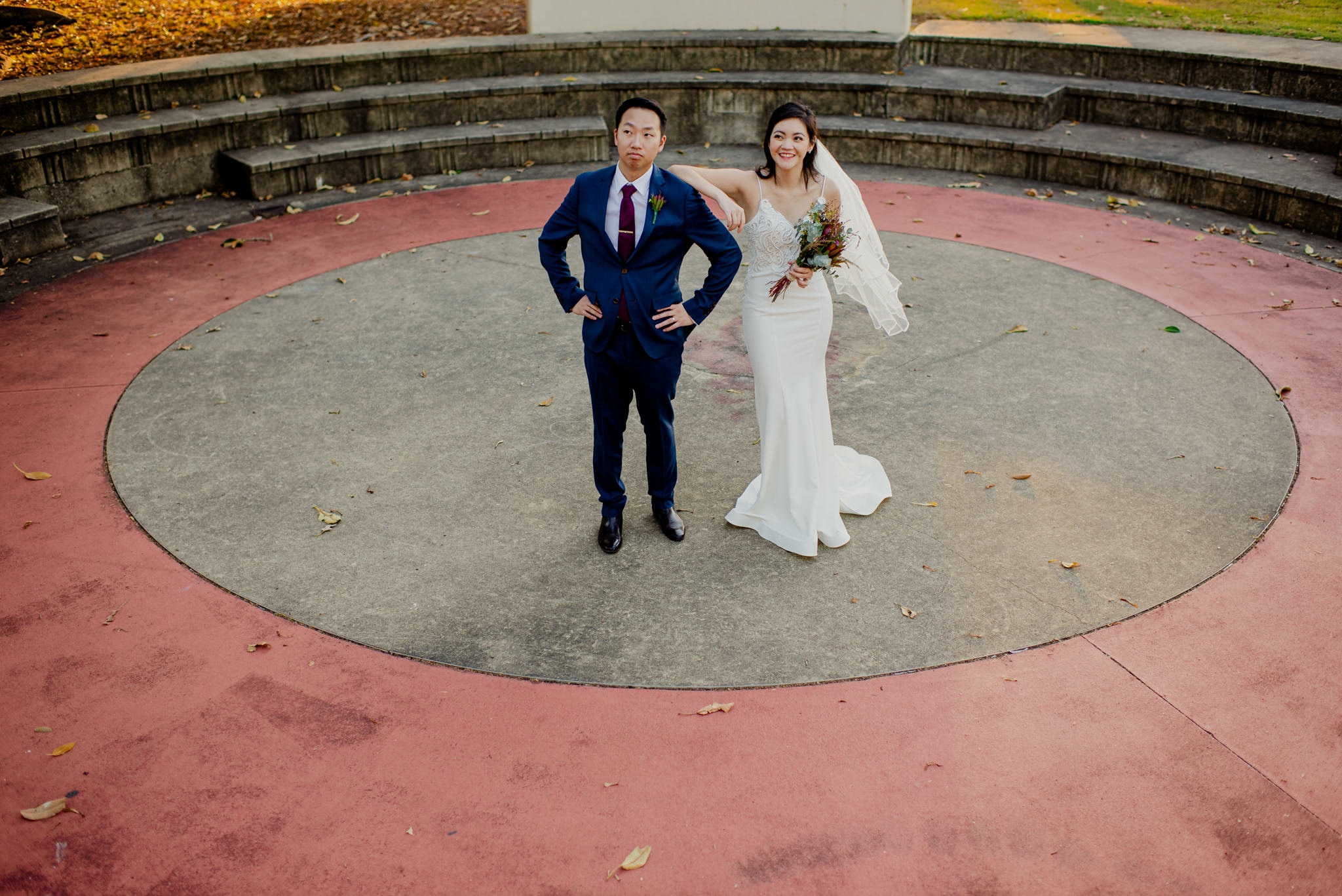 Two newlyweds pose on a large concrete circle enveloped by a red concrete ring