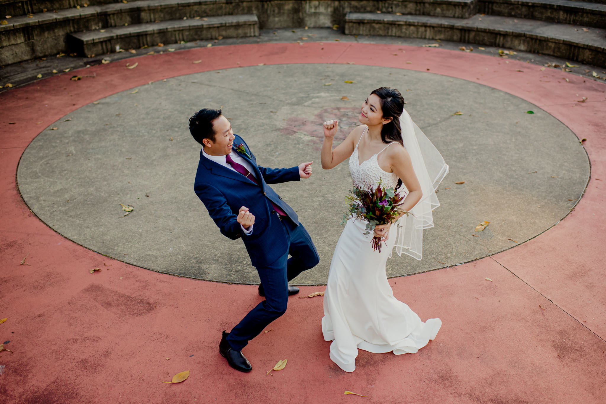 A bride and groom smile and dance on a large concrete circle