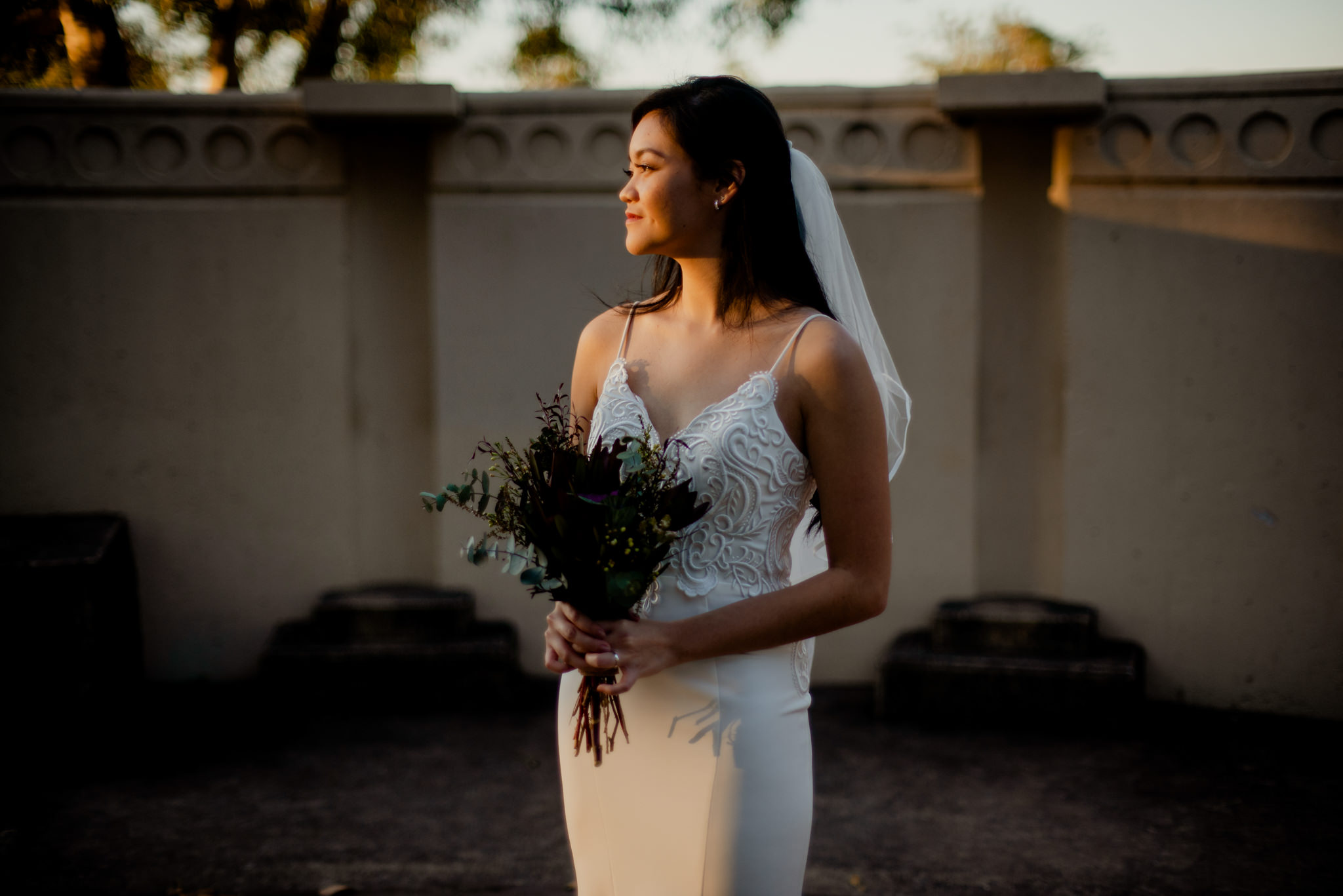 A bride poses with her wedding bouquet in a splash of golden sunlight