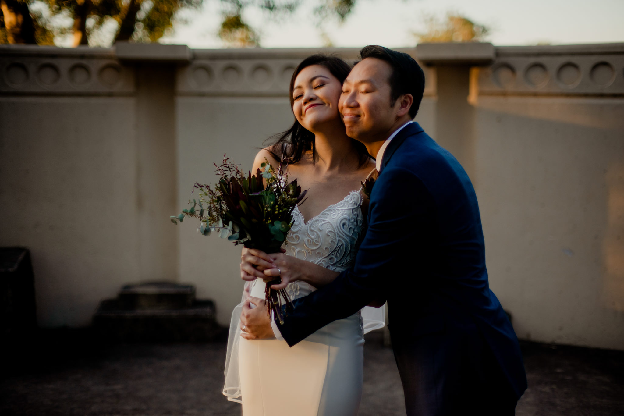 A bride and groom smile and hug in a ray of afternoon sun
