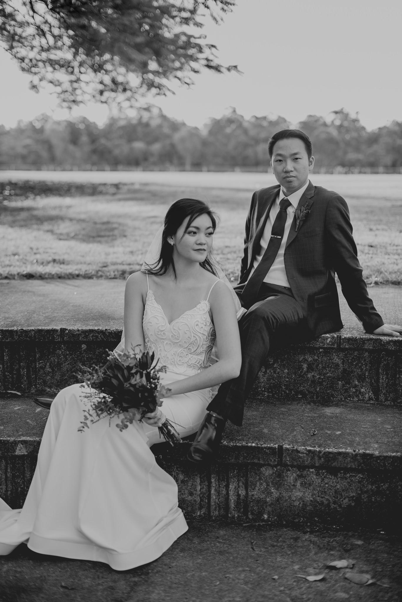 A bride and groom sit on concrete steps for a bridal portrait