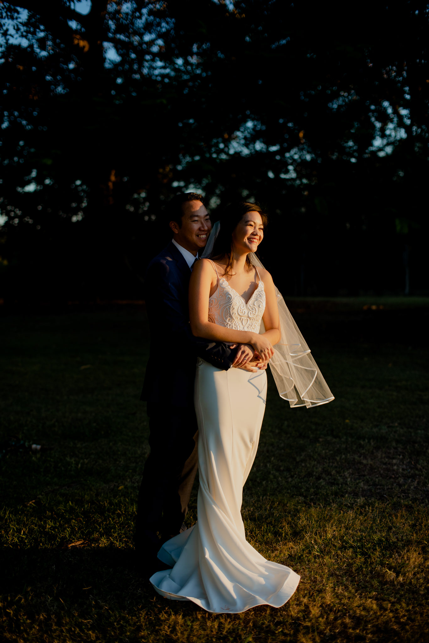 A bride being hugged by her groom as she stands in bright golden afternoon light