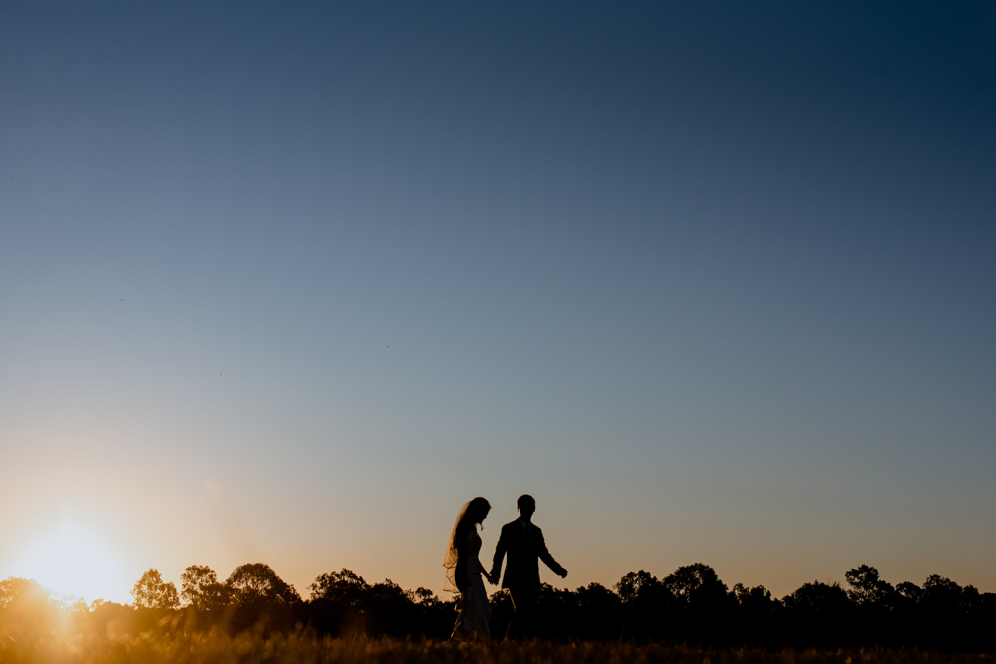 A silhouette of a bride and groom holding hands and walking in the afternoon, in front of a clear open blue sky