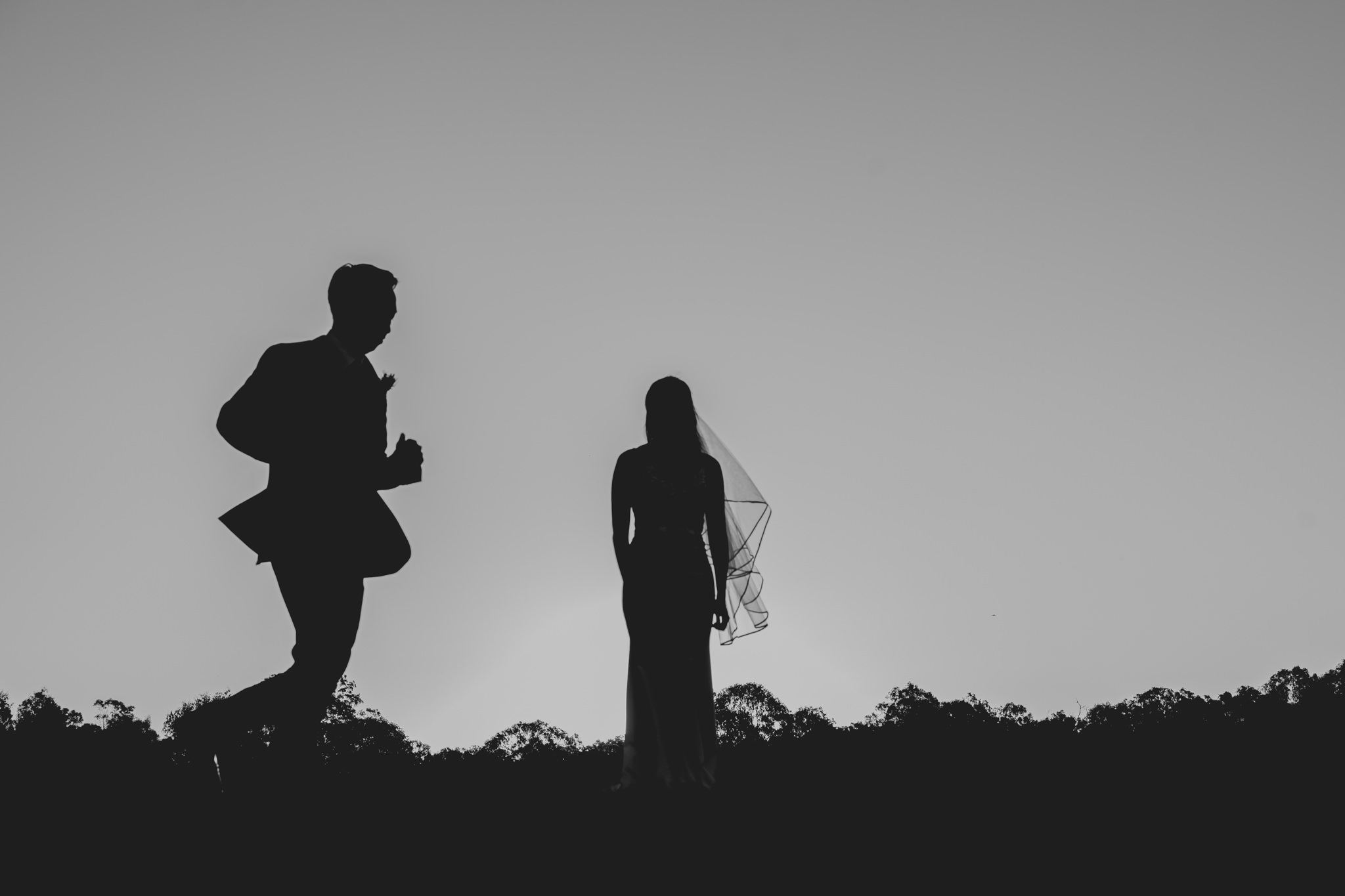 Silhouette of a groom running as a bride stands in the centre of a clear sky