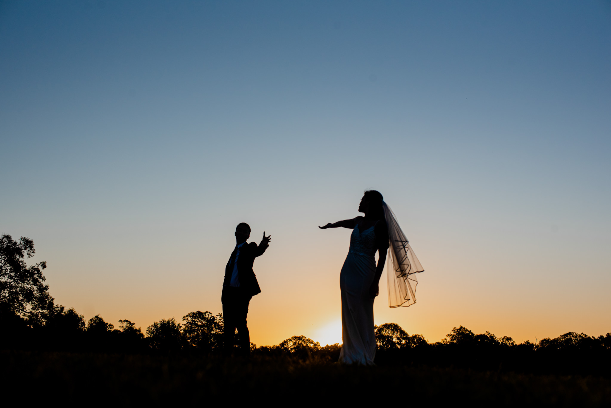 Silhouette of a bride and groom during sunset, reaching out towards each other