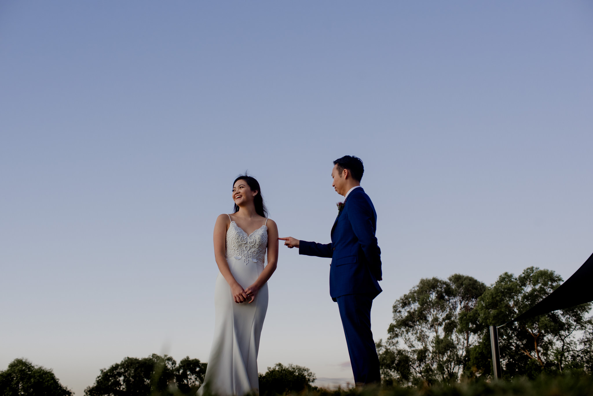 A bride laughs and faces away as her groom pokes her upper arm