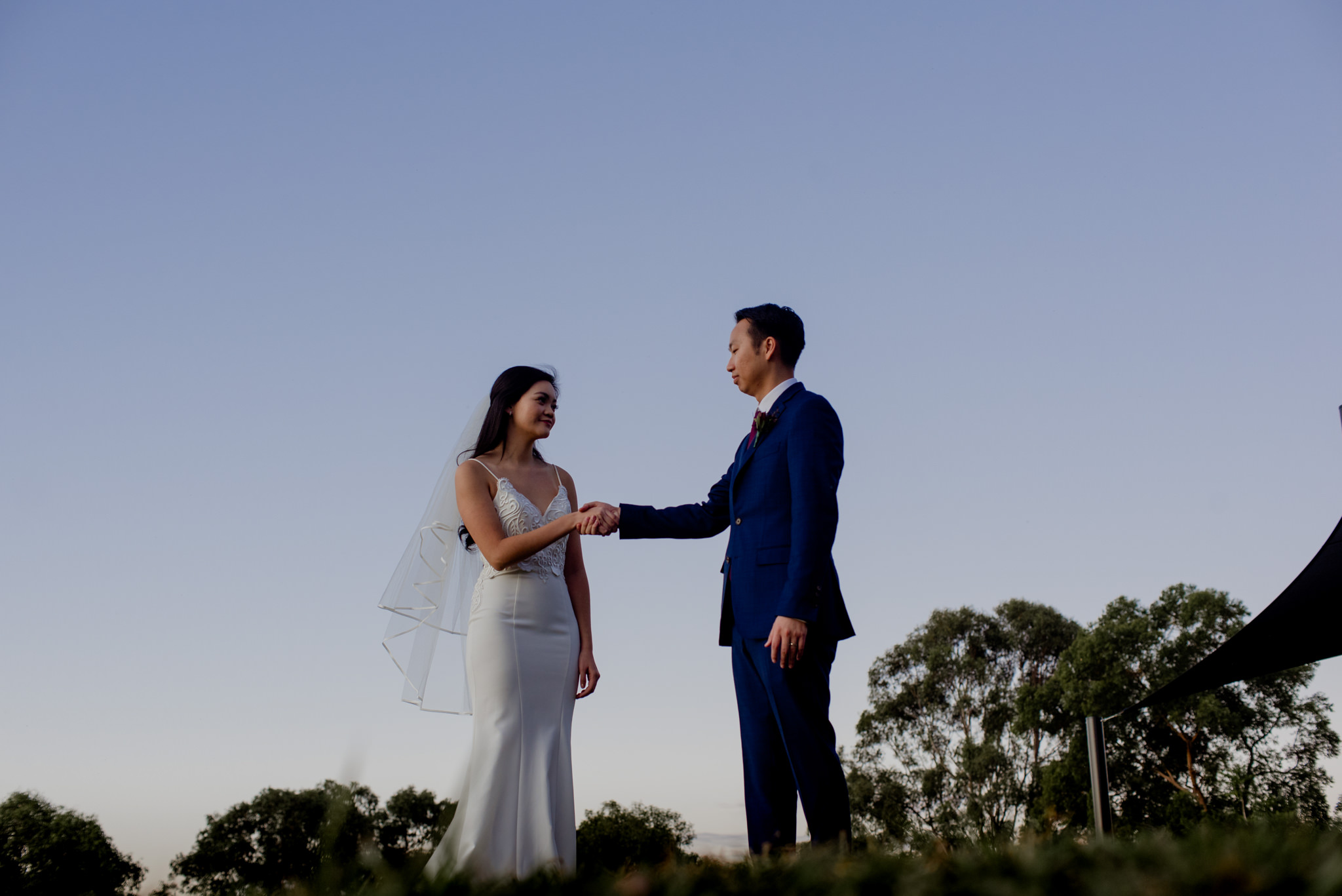 A bride and groom shake hands during twilight