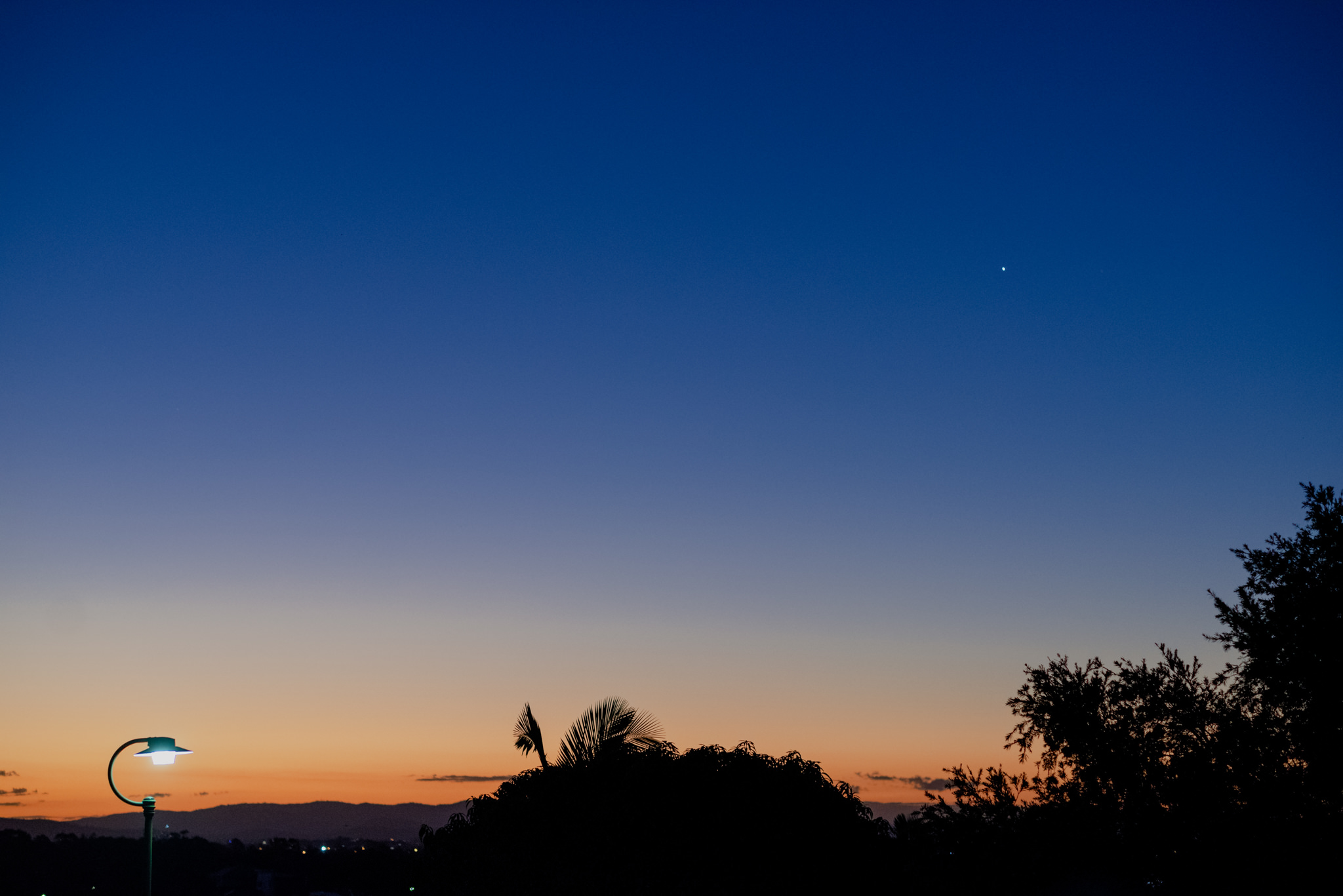 A rich orange and blue sky with a single star shining