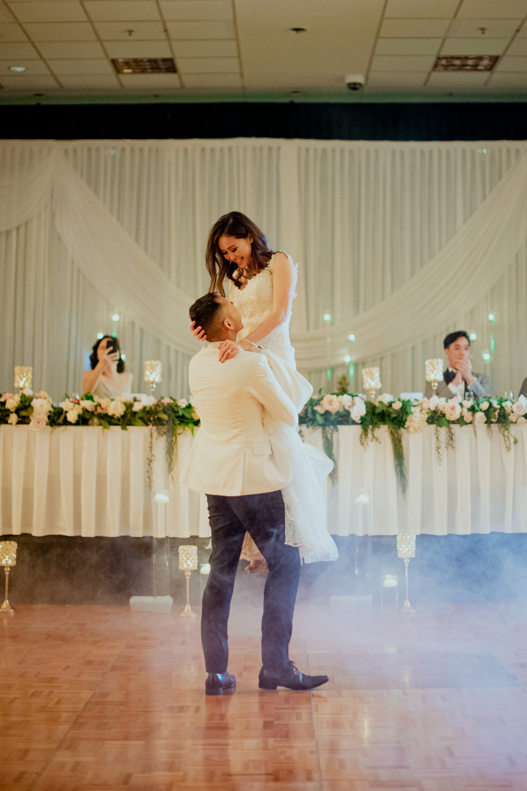 A bride being lifted in the air while smoke covers the dance floor