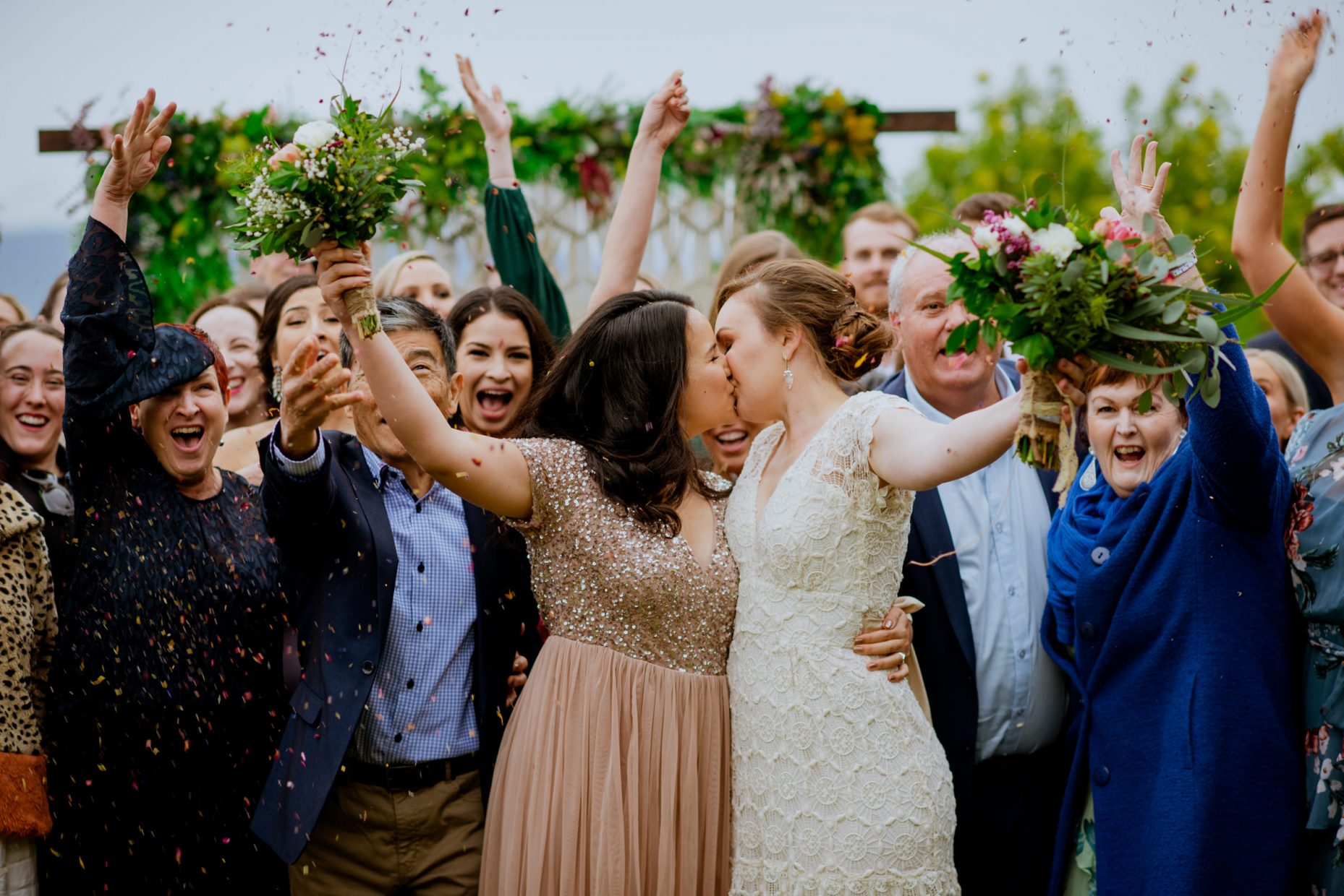 A same-sex couple kiss and hold their bouquets up as wedding guests all cheer