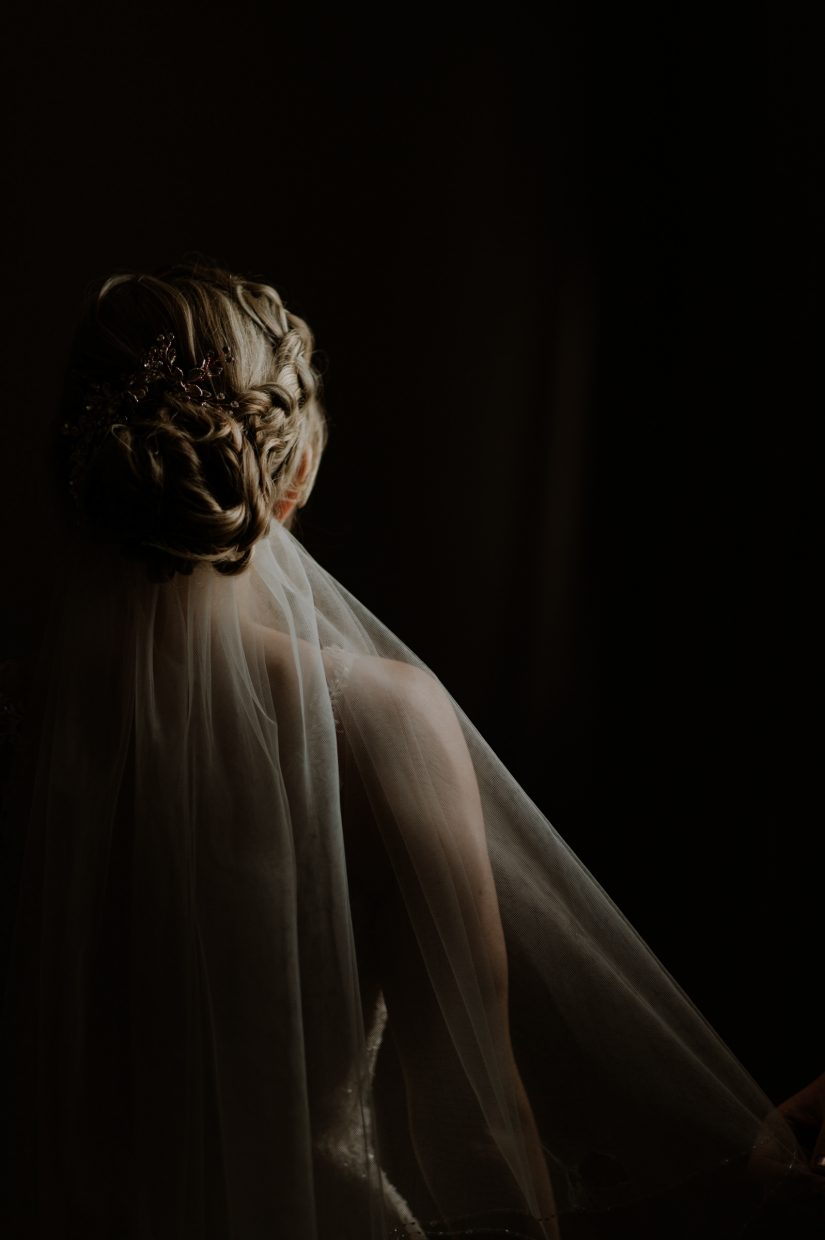 A bride's hair, shoulder and veil are gently lit against a dark background