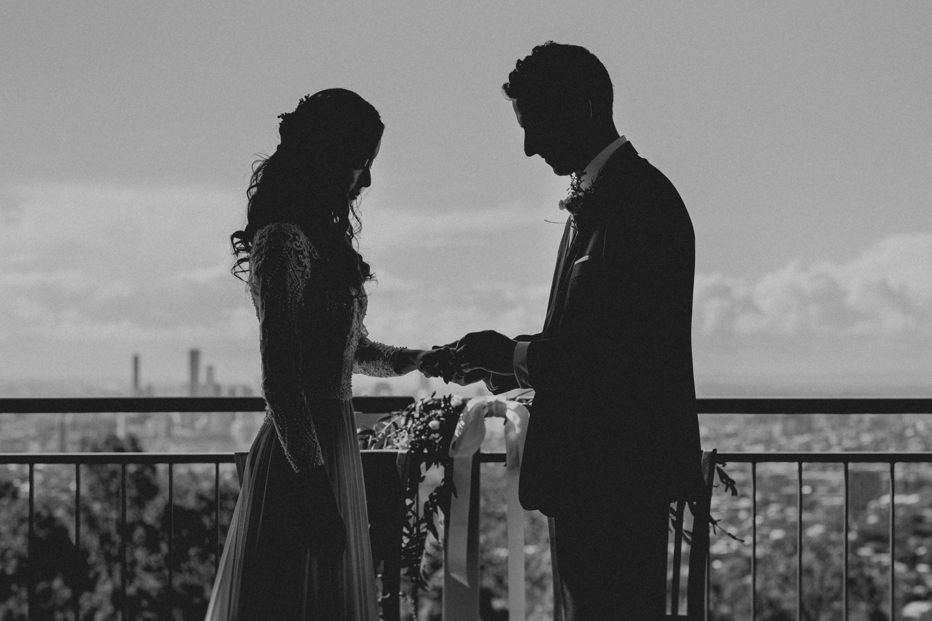 A silhouetted groom holds the hands of a silhouetted bride during their wedding ceremony
