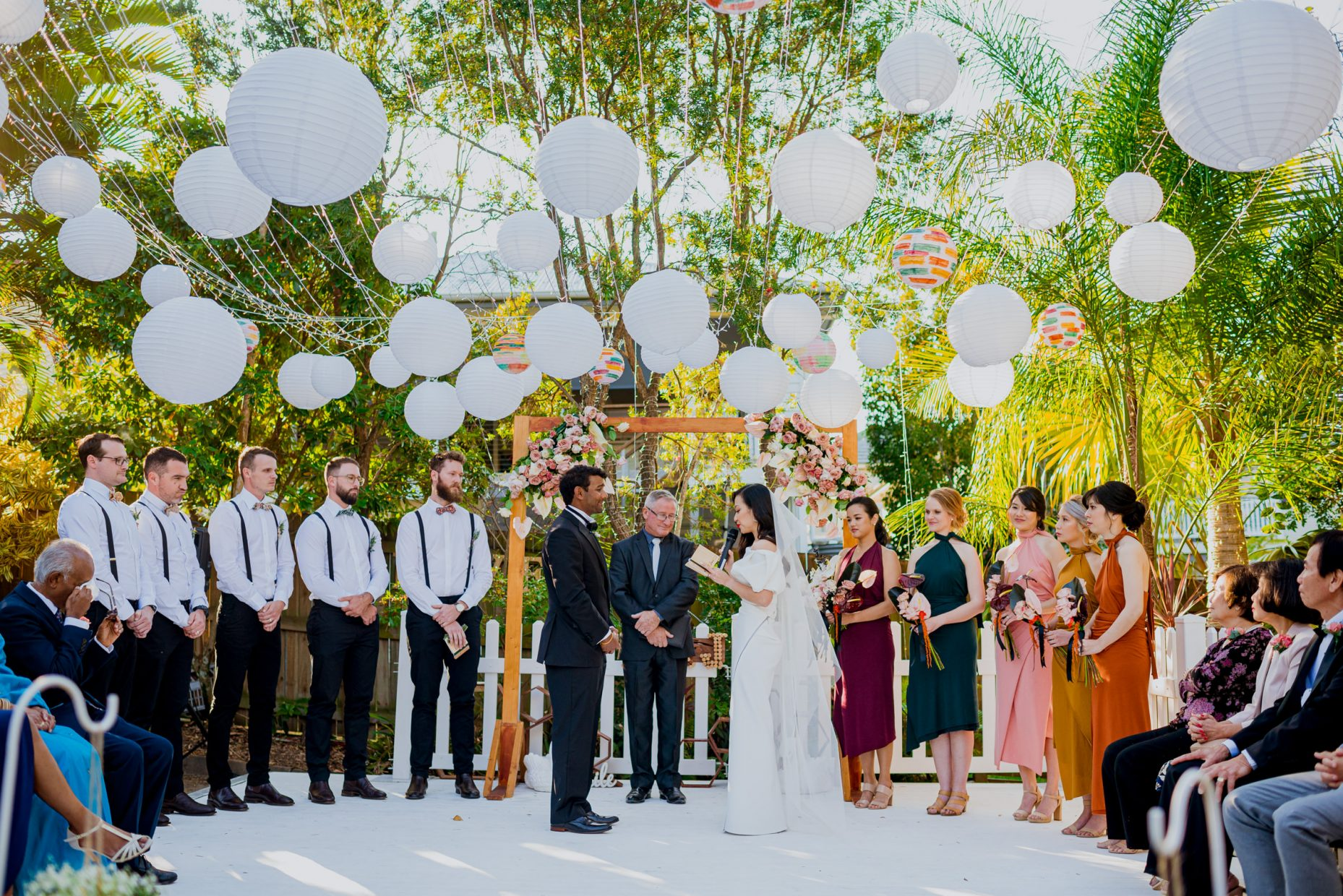 A colourful outdoor wedding ceremony held on a white stage with white lanterns overheard