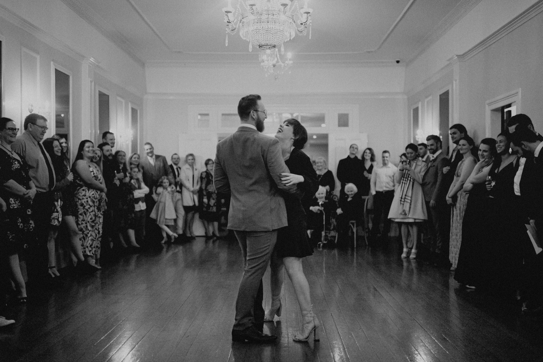 A bride and groom laugh as they dance in the middle of a hall with onlookers surrounding them